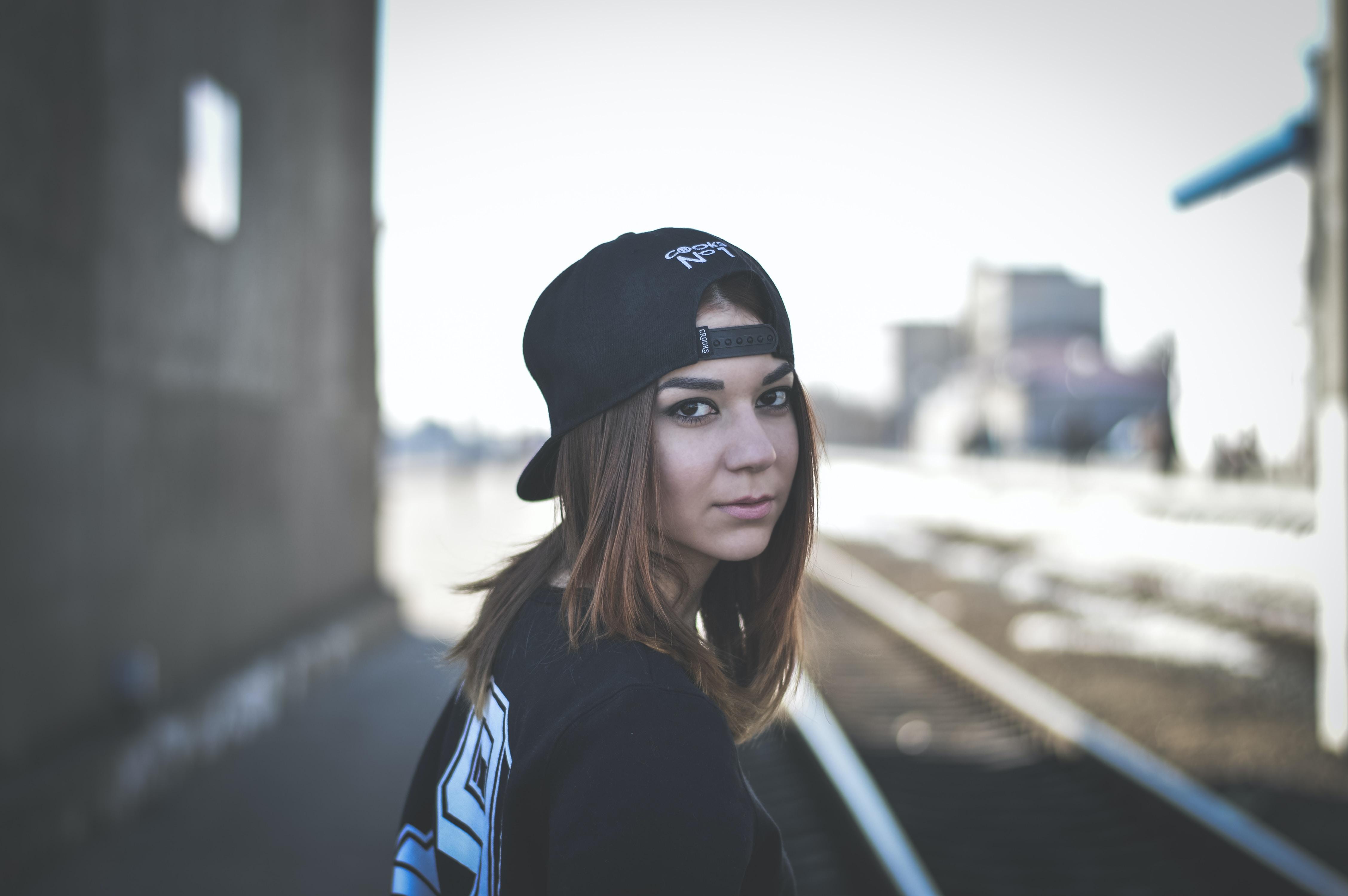 woman wearing black snapback cap looking back