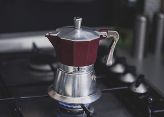 maroon and silver-colored kettle on stove