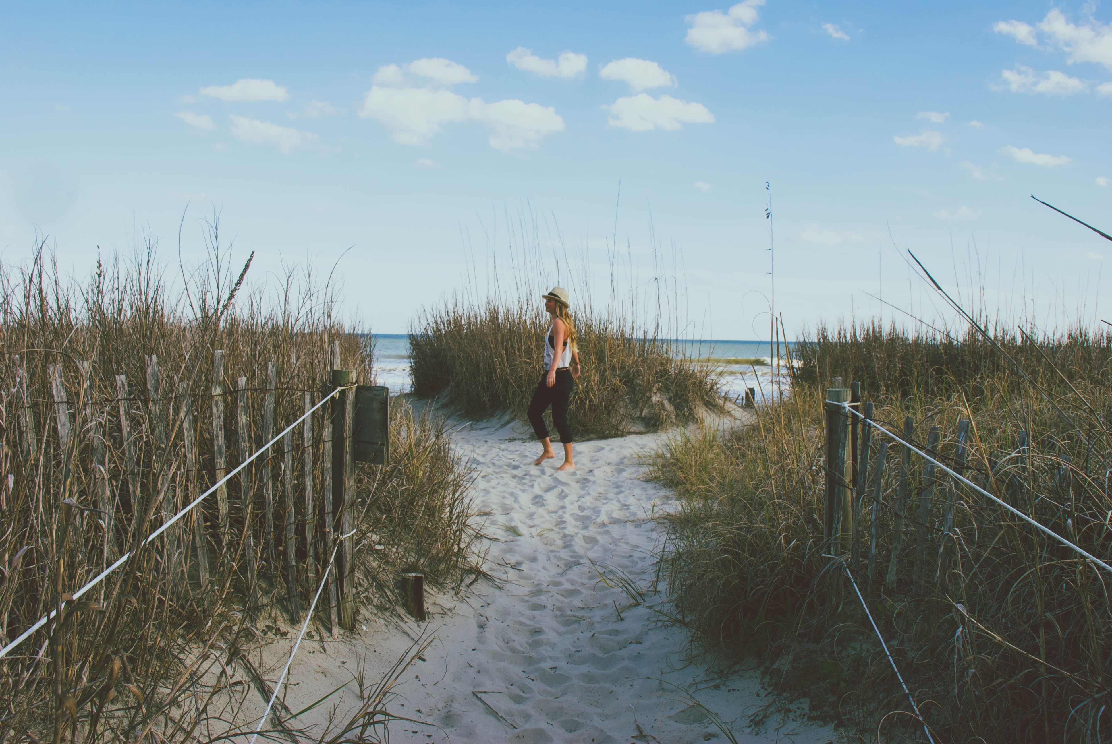 Woman with a hat on the grass covered sand beach at Myrtle Beach