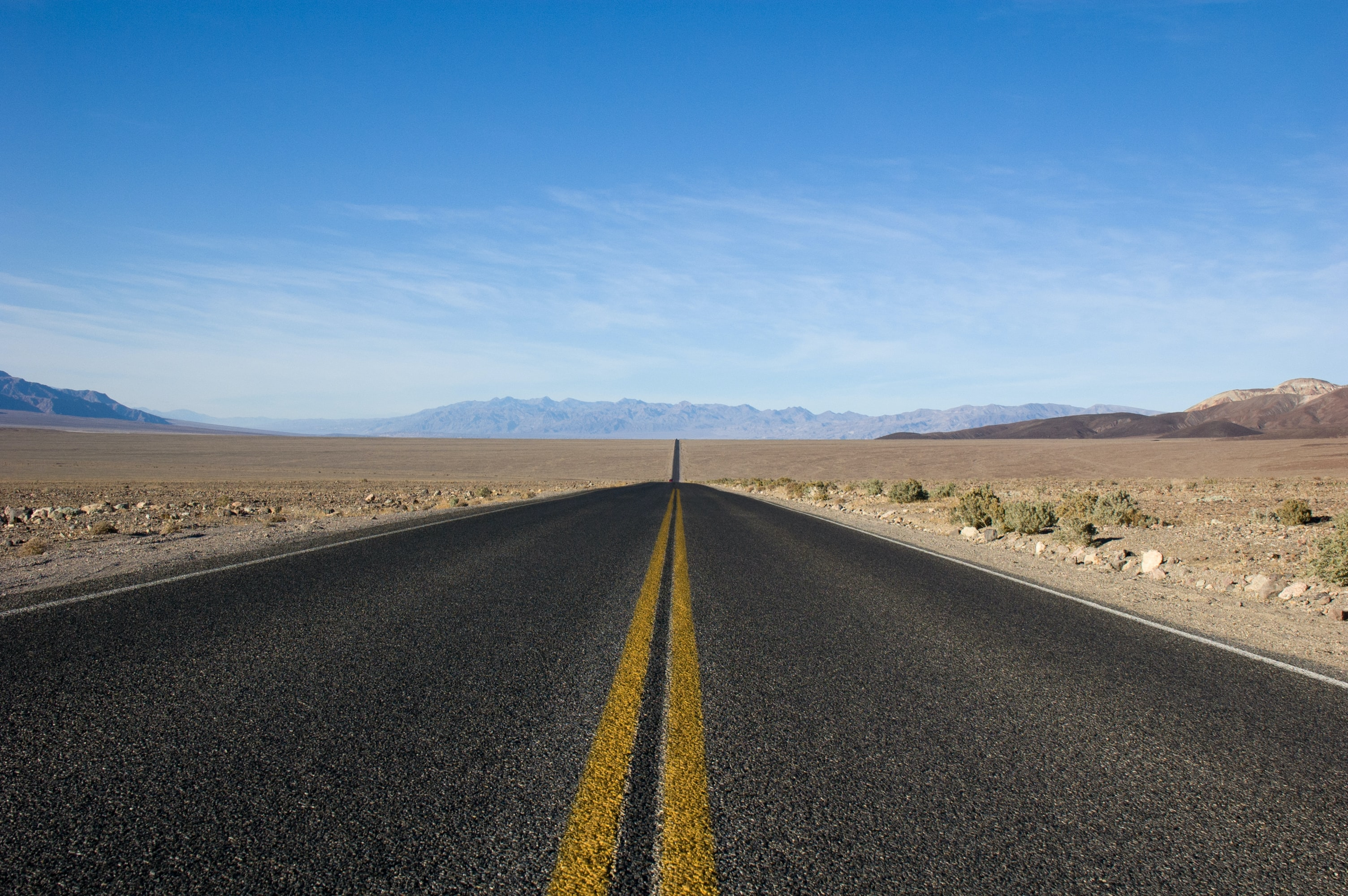 straight asphalt road between desert at daytime