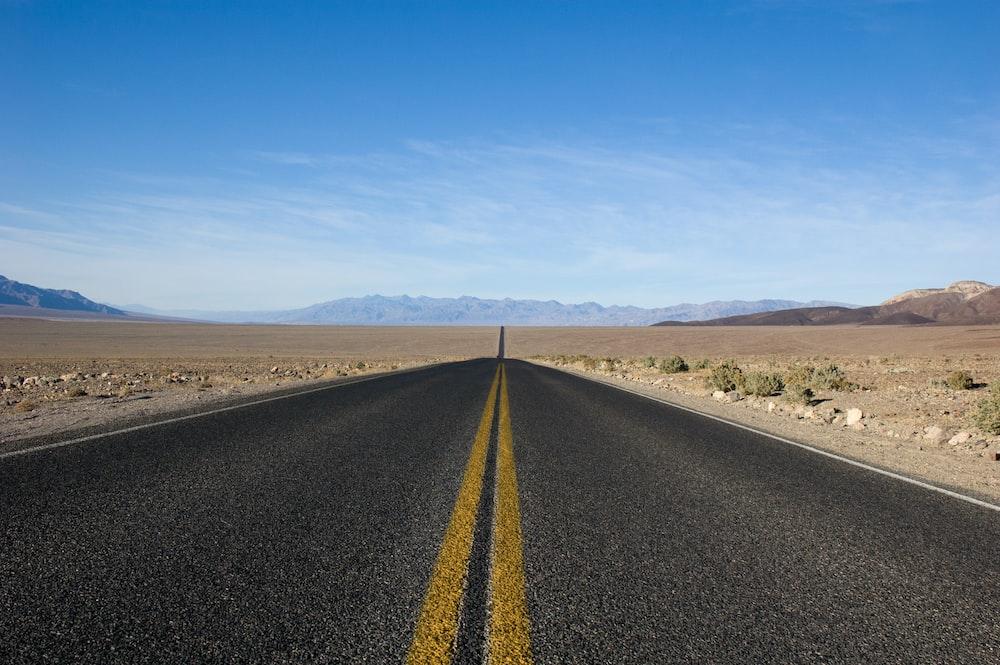 straight asphalt road between desert at daytime
