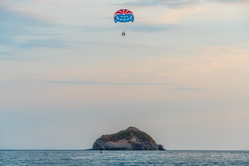 two people paragliding towards islet