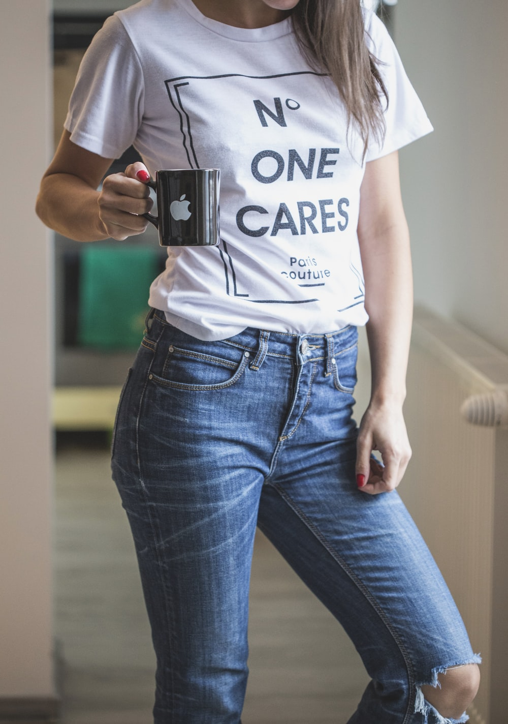 woman in white crew neck t-shirt and blue denim jeans holding black camera