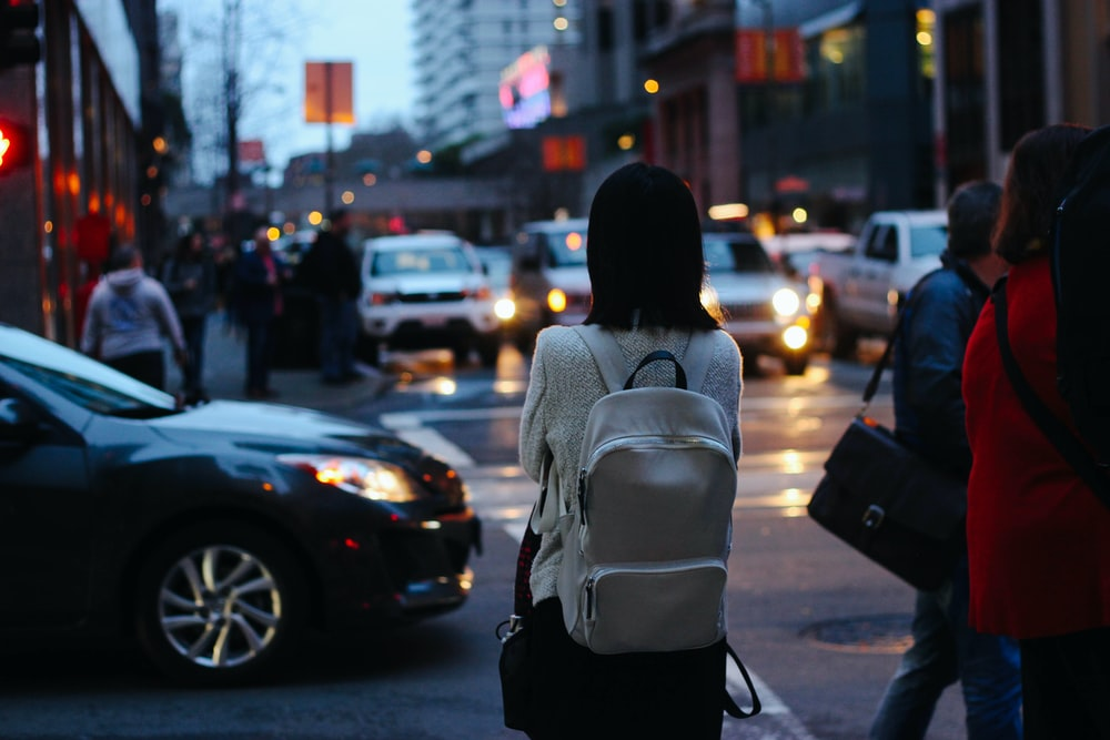woman wearing grey shirt and white backpack facing car on street