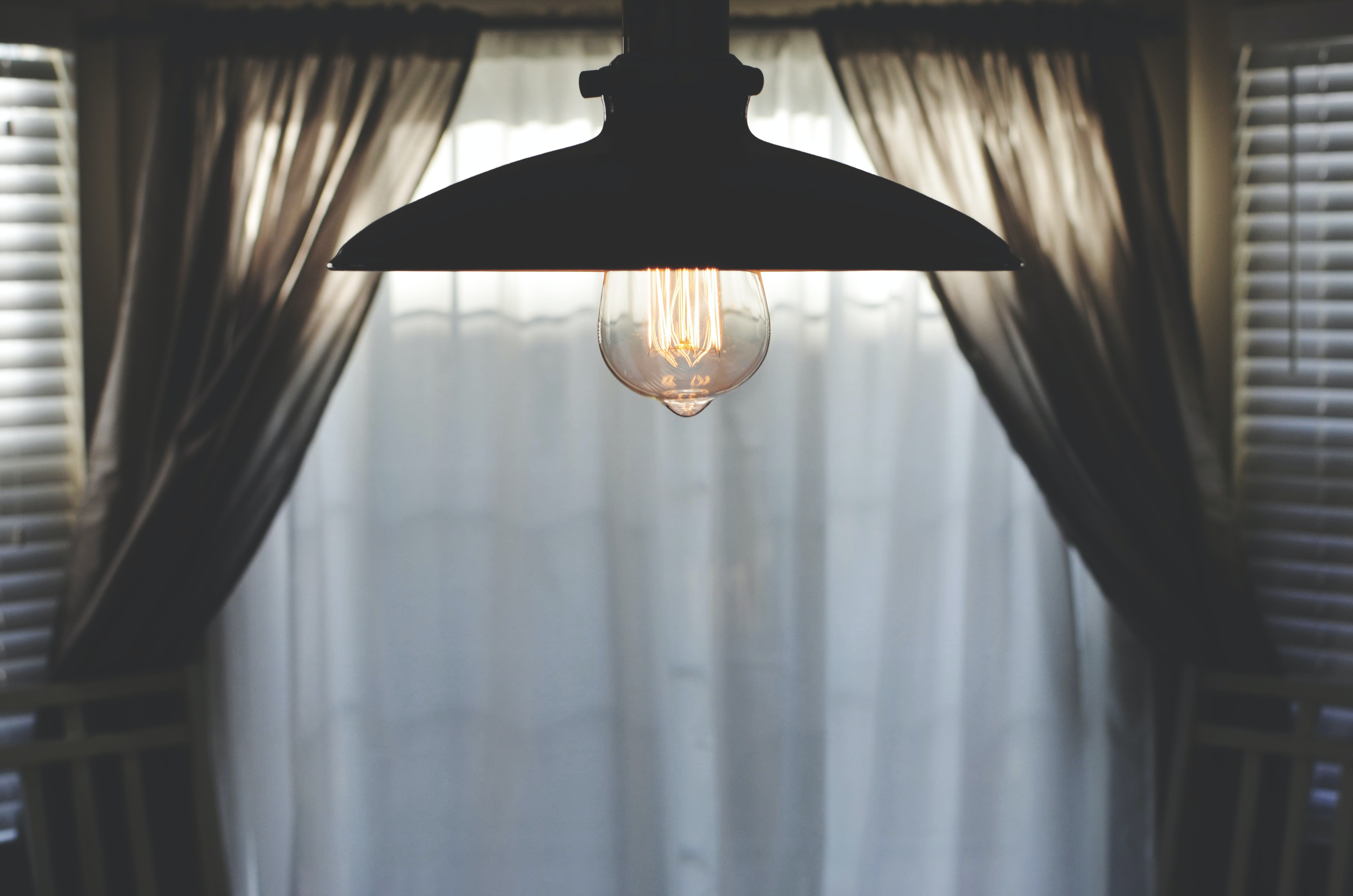 black pendant lamp in room with curtain