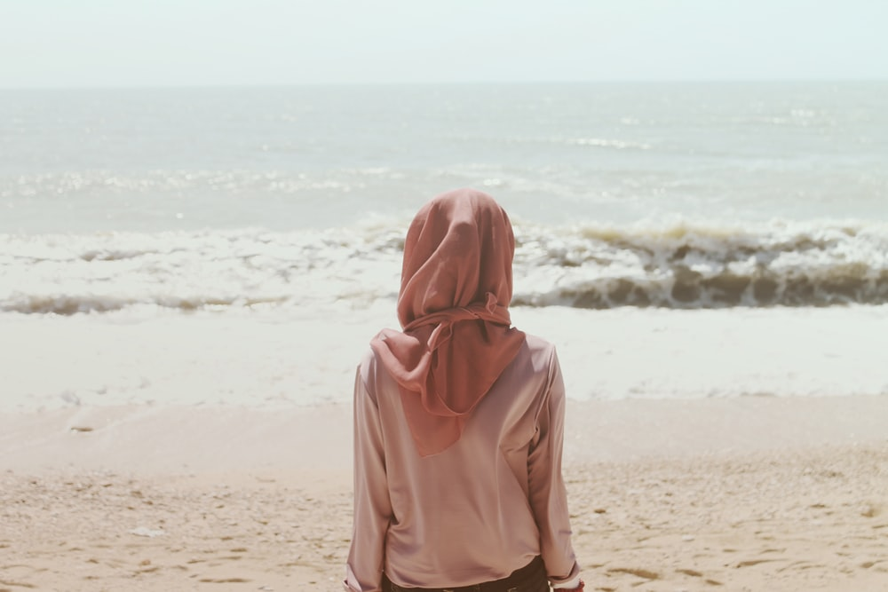 woman sitting on beach shore in front of sea waves