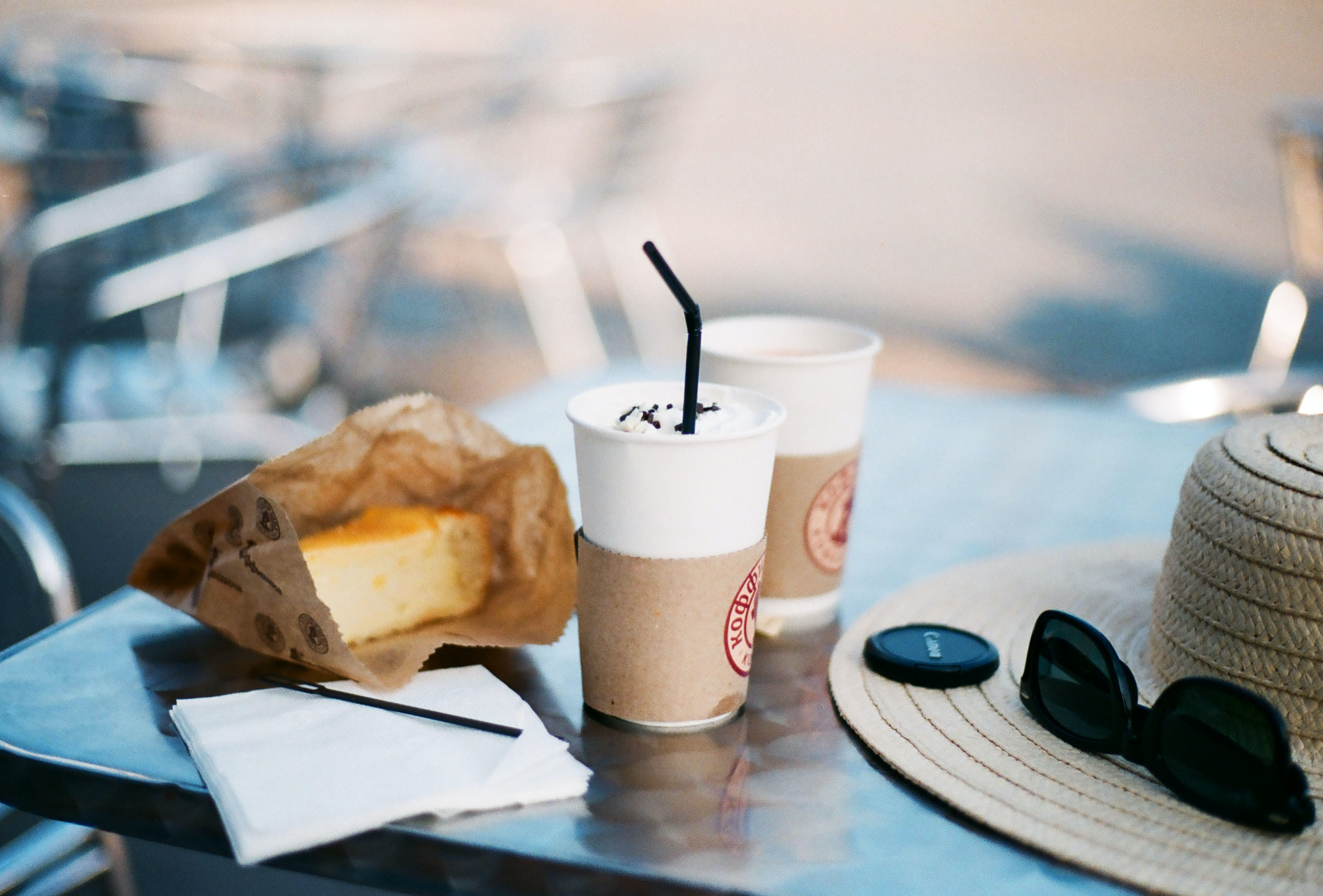 An outdoor table with iced coffee, a piece of cake, a hat and black sunglasses