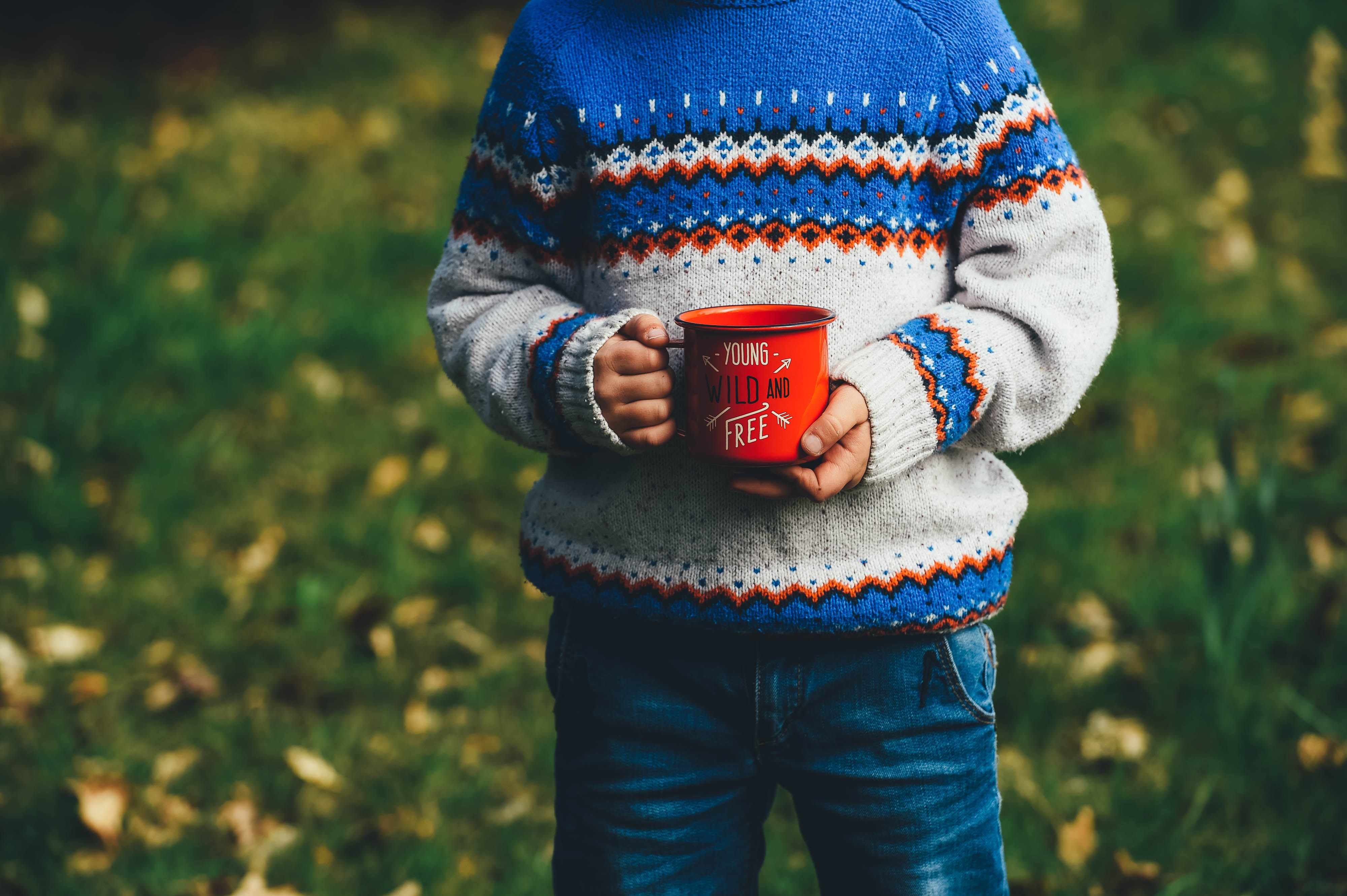 """A child holding a red enamel cup with """"young, wild and free"""" written on it"""