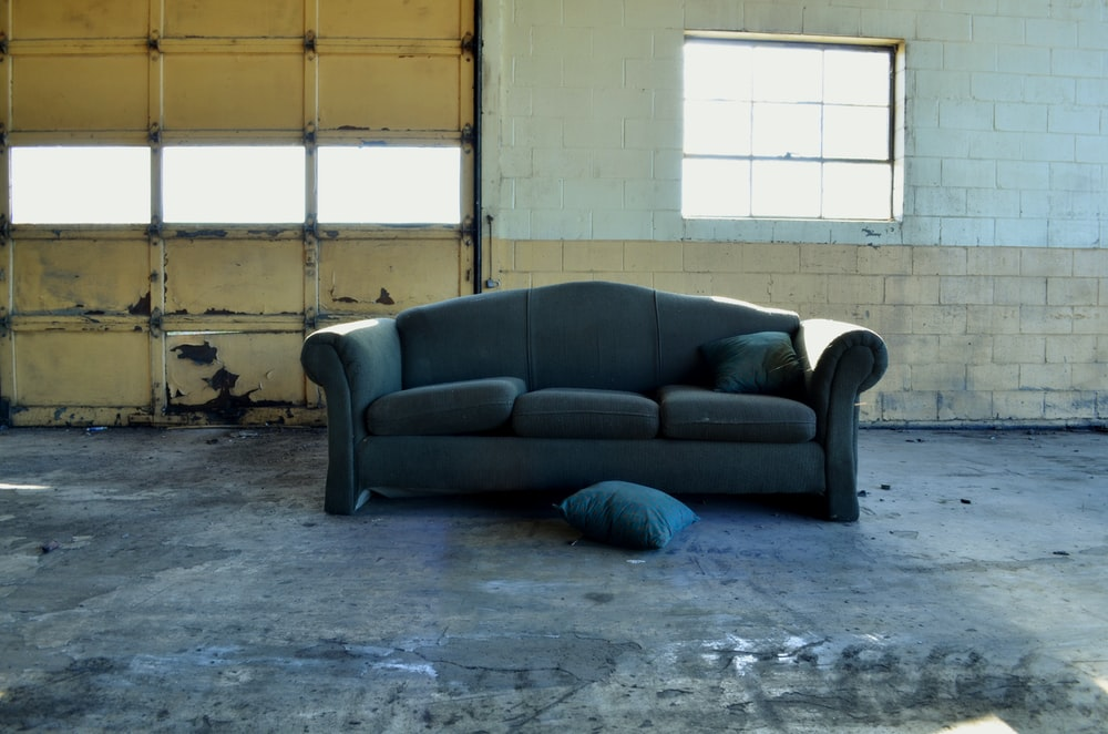 black fabric 3-seat sofa in front of wall and garage door