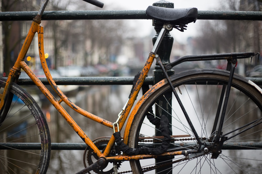 orange bike parked beside bridge grills