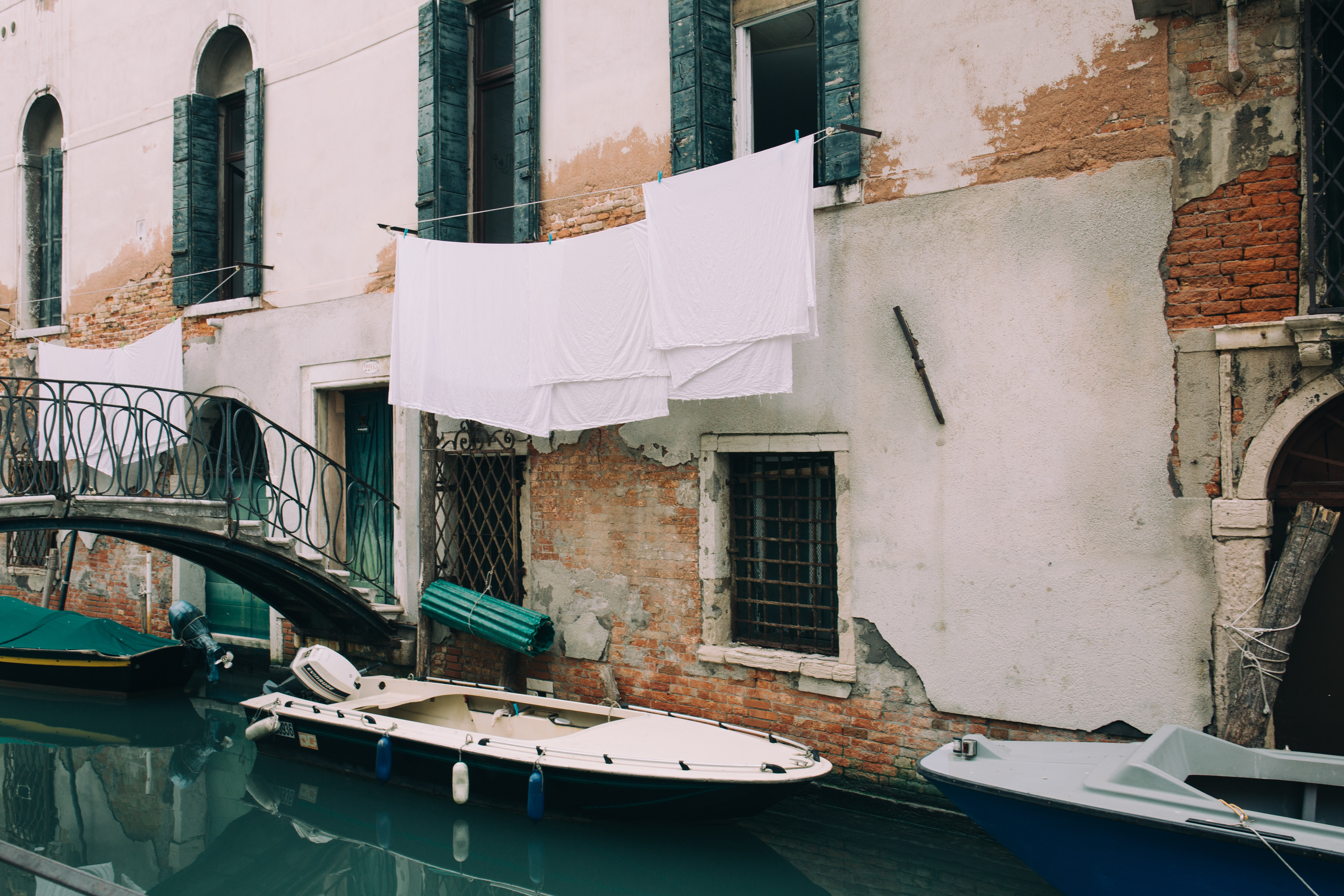 white and blue motorboat near wall during daytime