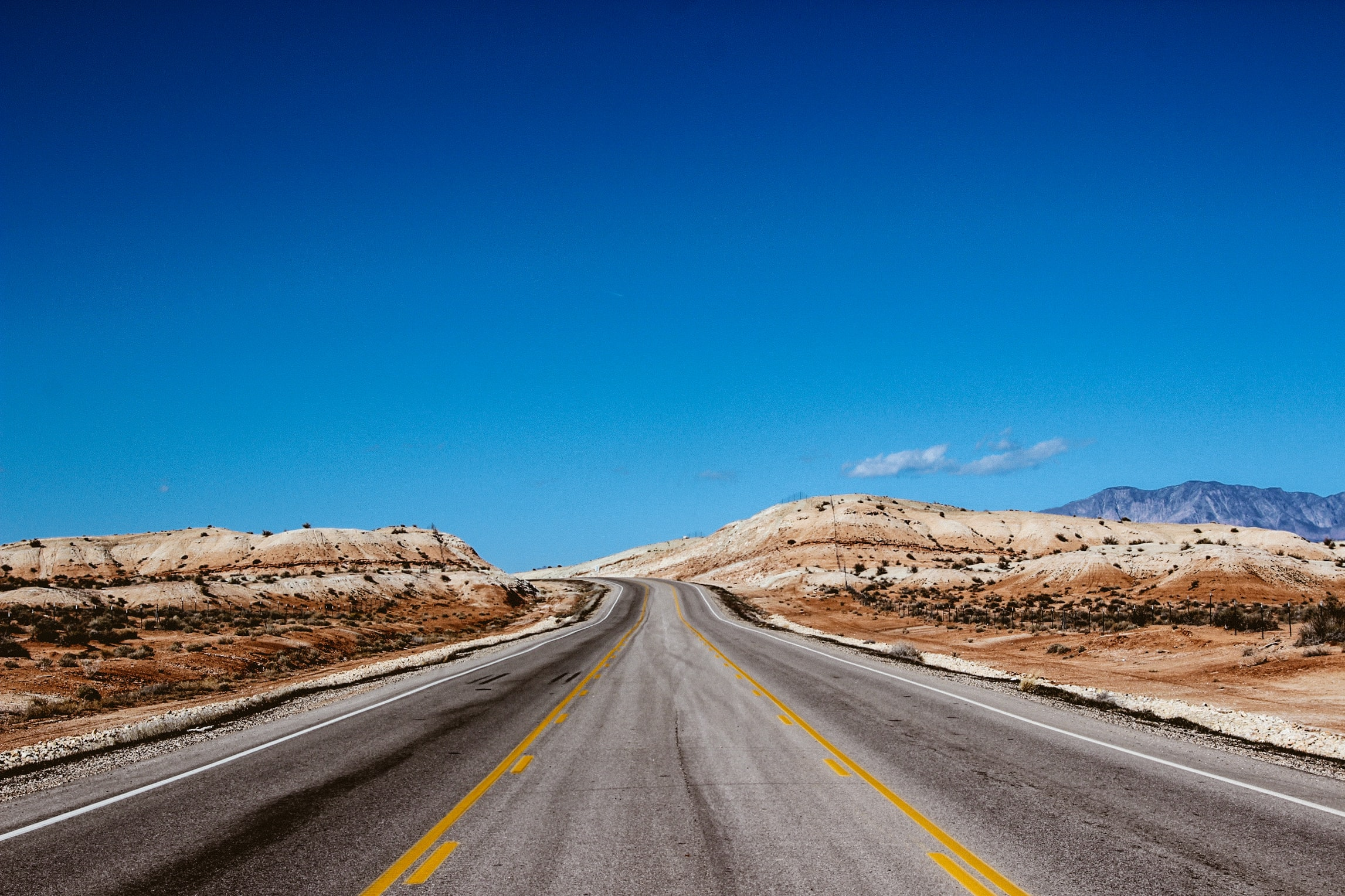 A desert road that goes to the horizon on a day with blue skies