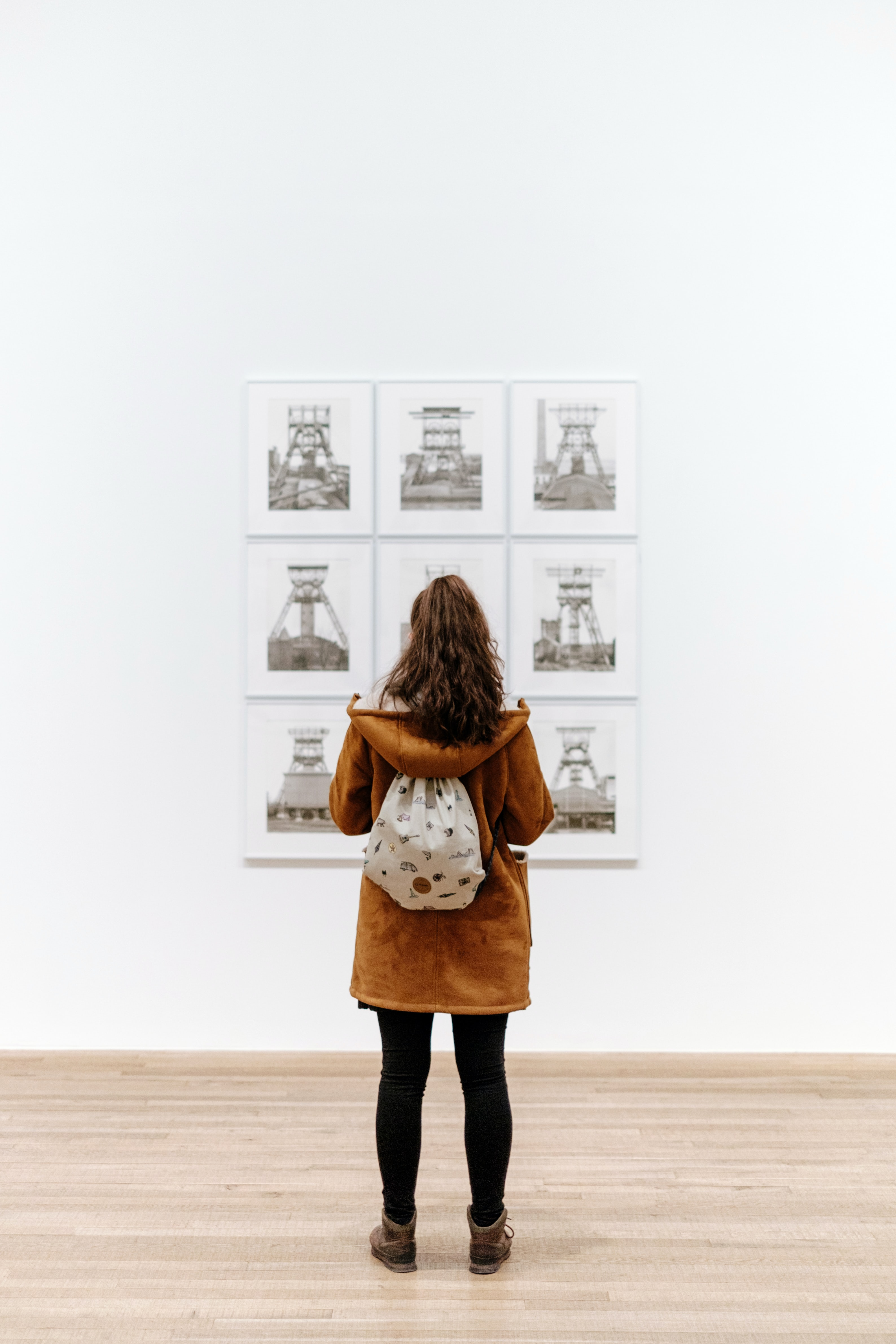 Young woman with brown hooded jacket and backpack view artwork on white background at Tate Modern