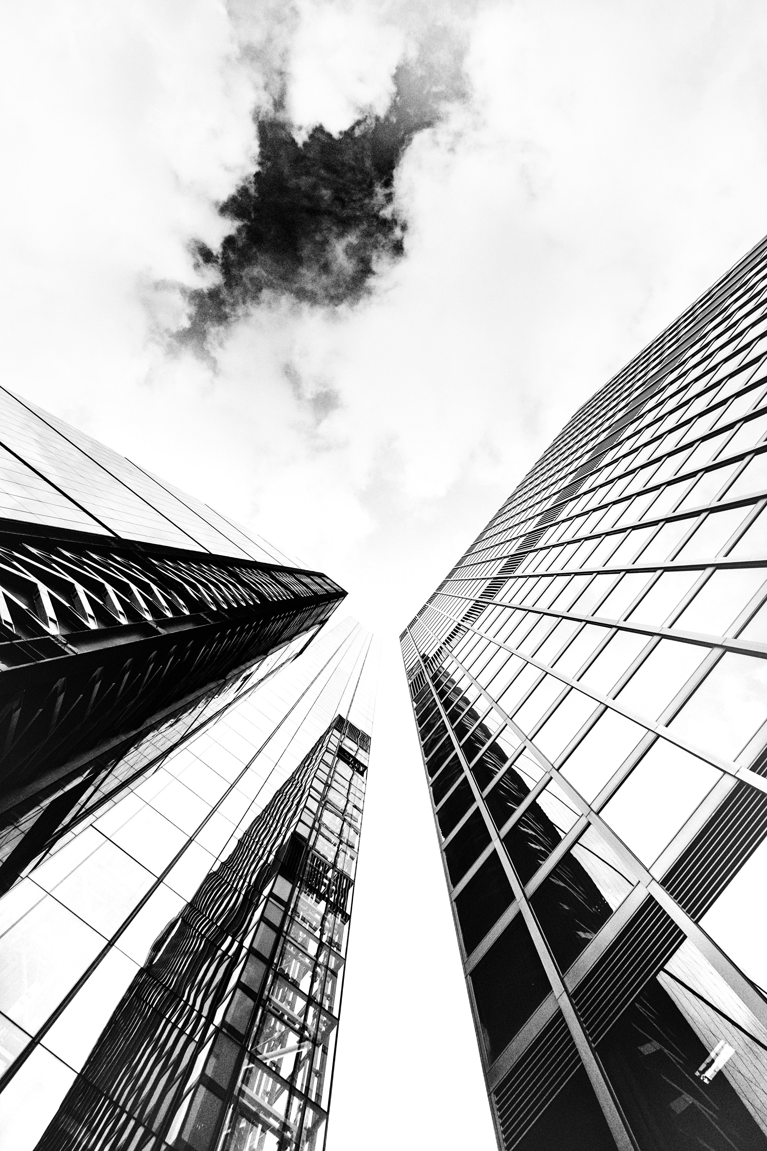 A low-angle monochrome shot of glass skyscraper facades under cloudy sky