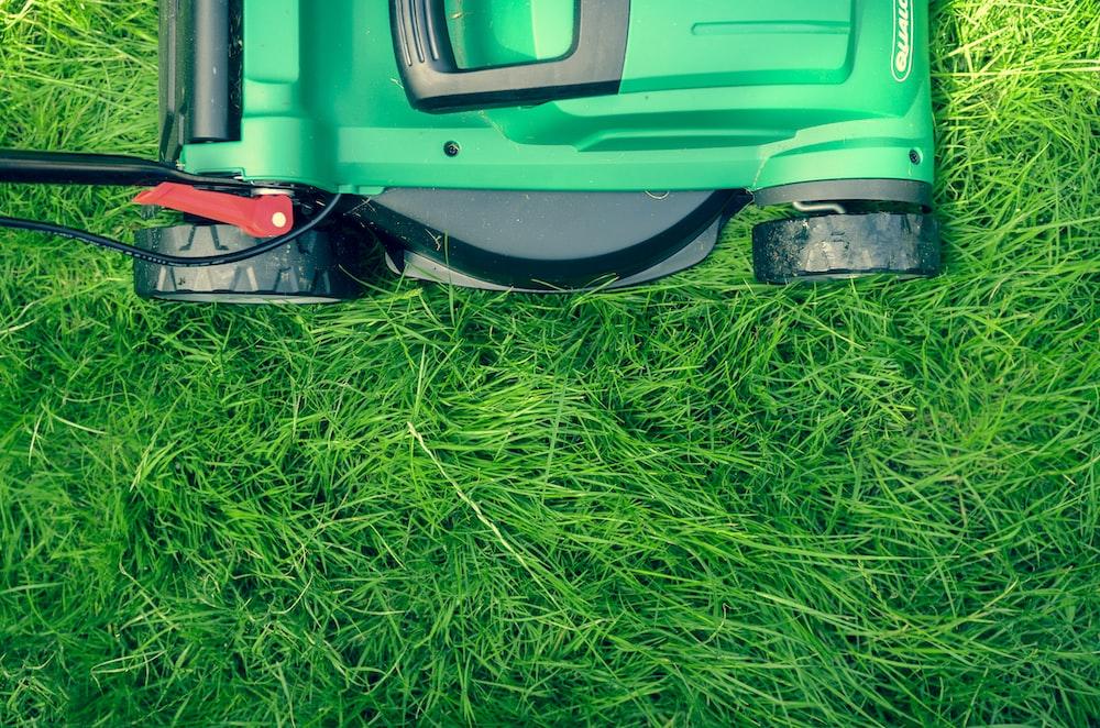 An overhead shot of a green lawnmower on green grass