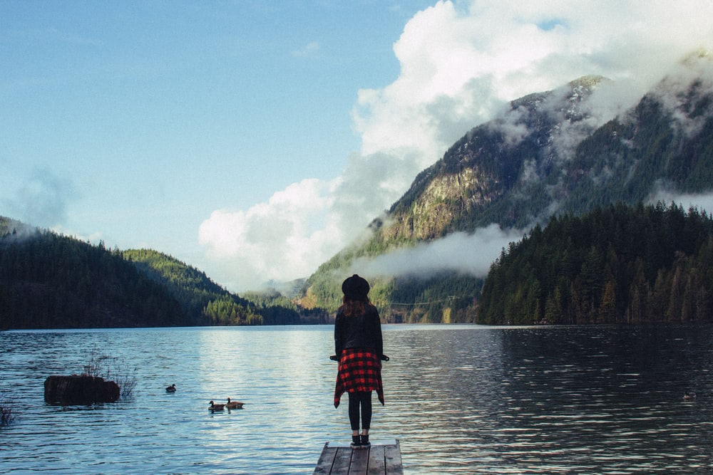 girl standing on dock surrounded by body of water