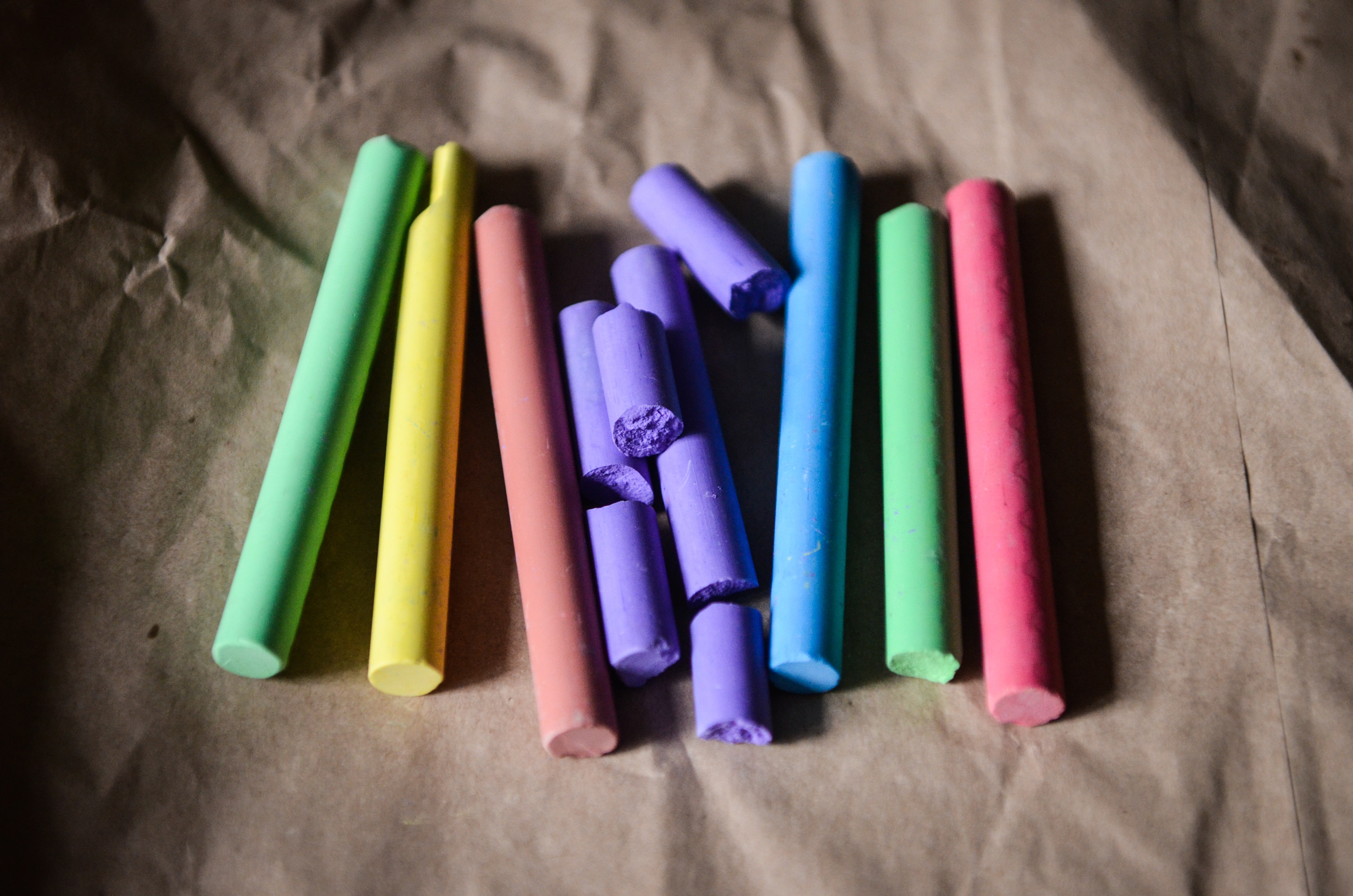 Close up of chalk crayons arranged in rainbow colours on baking paper