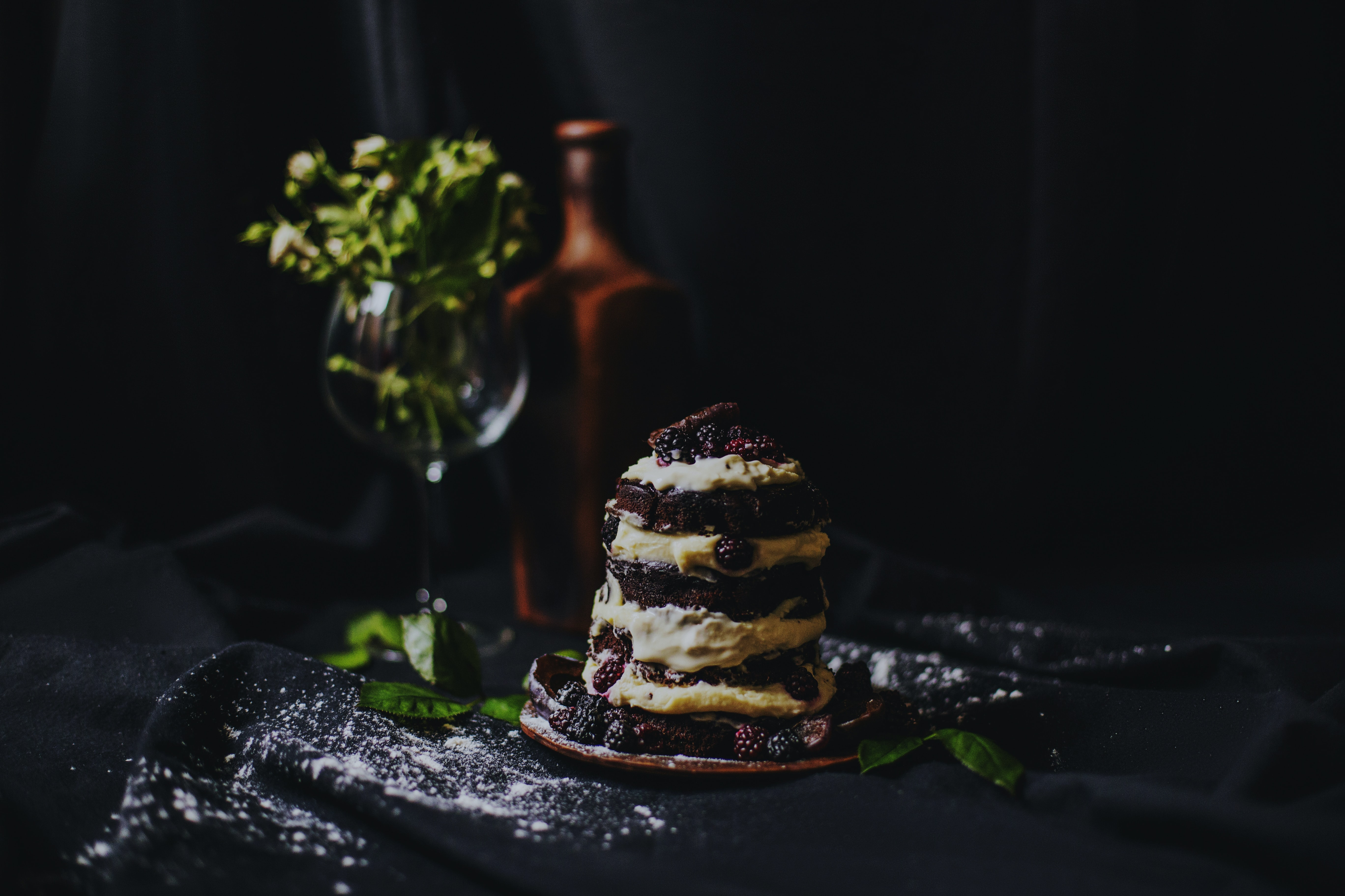 A tall cake and flowers on a table.