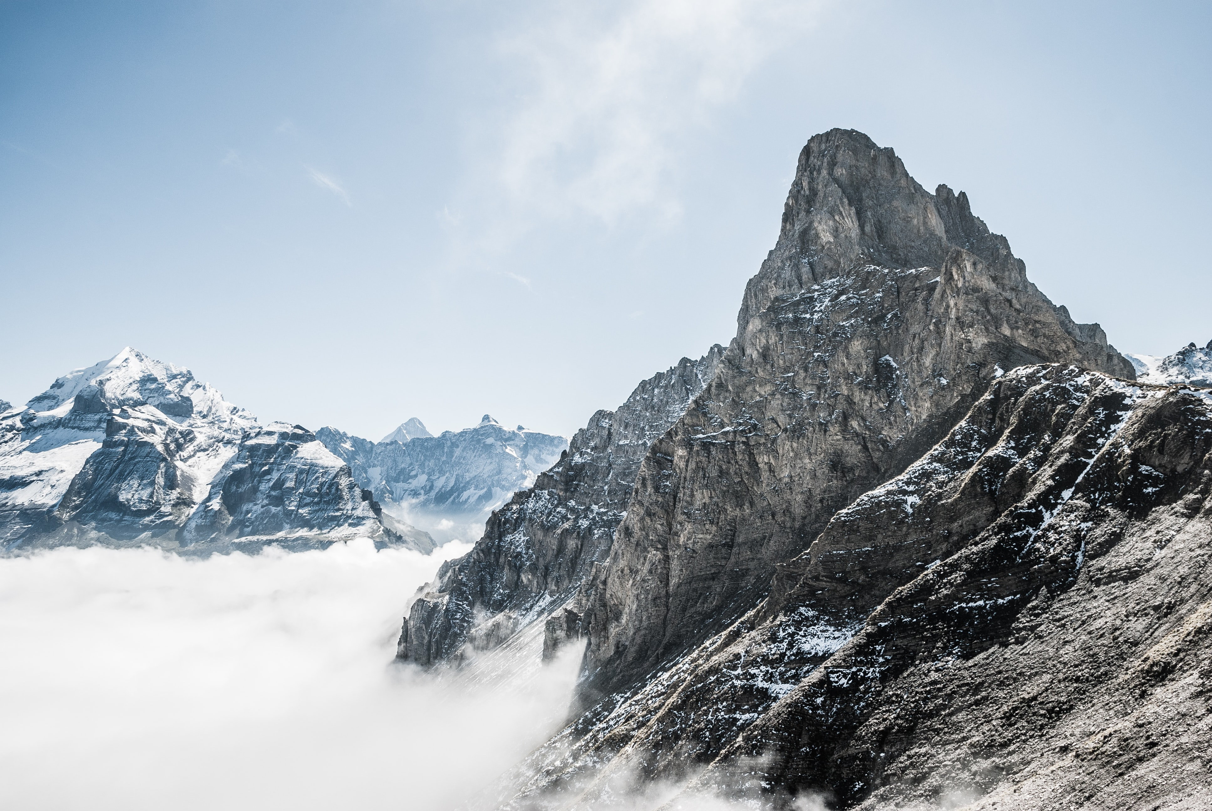 The snow covered Bunderspitz mountain peak rising above the clouds