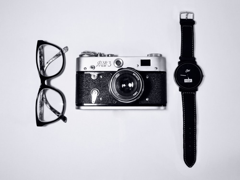 black and silver camera; eyeglasses with black frames; black analog watch