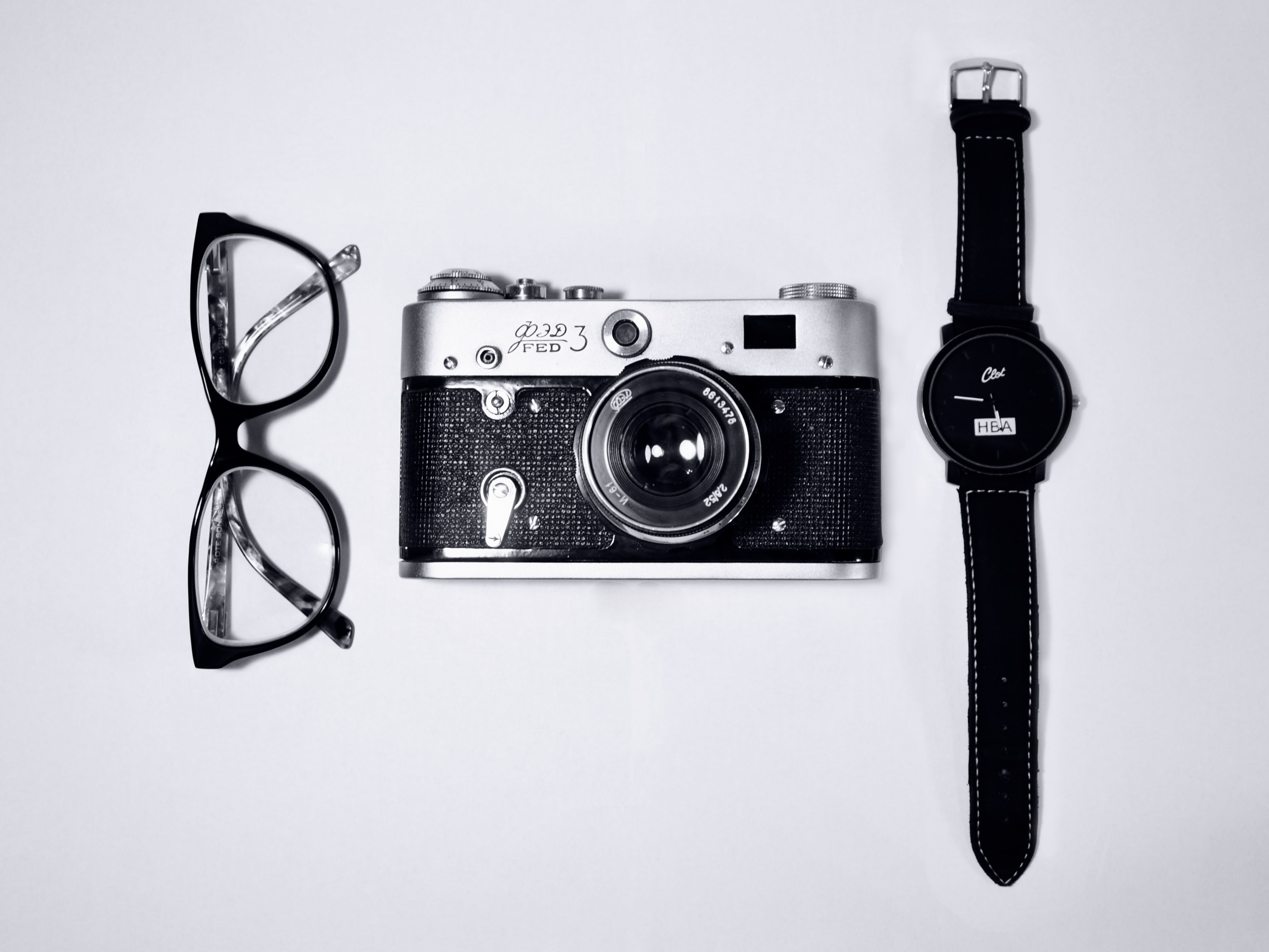 black and silver camera; eyeglasses with black frames; black analog watch