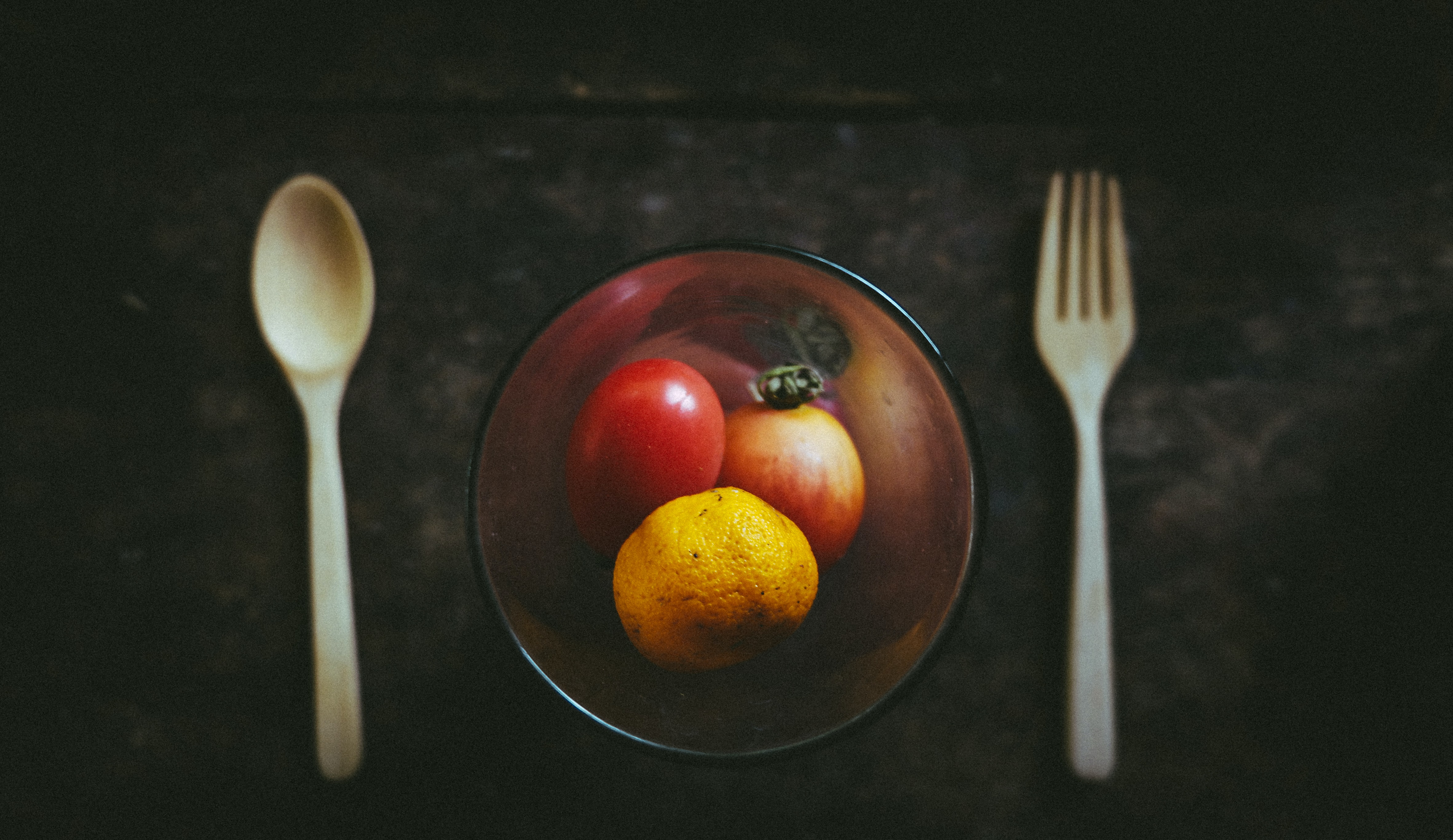 Tomato, orange, and vegetable in a bowl next to a fork and knife