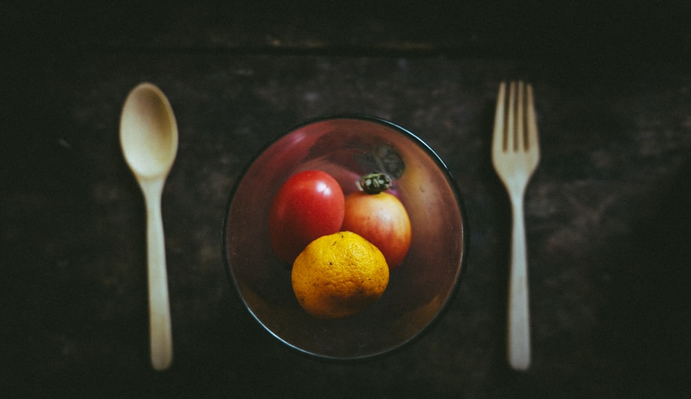 amber glass bowl with fruits besides white spoon and fork