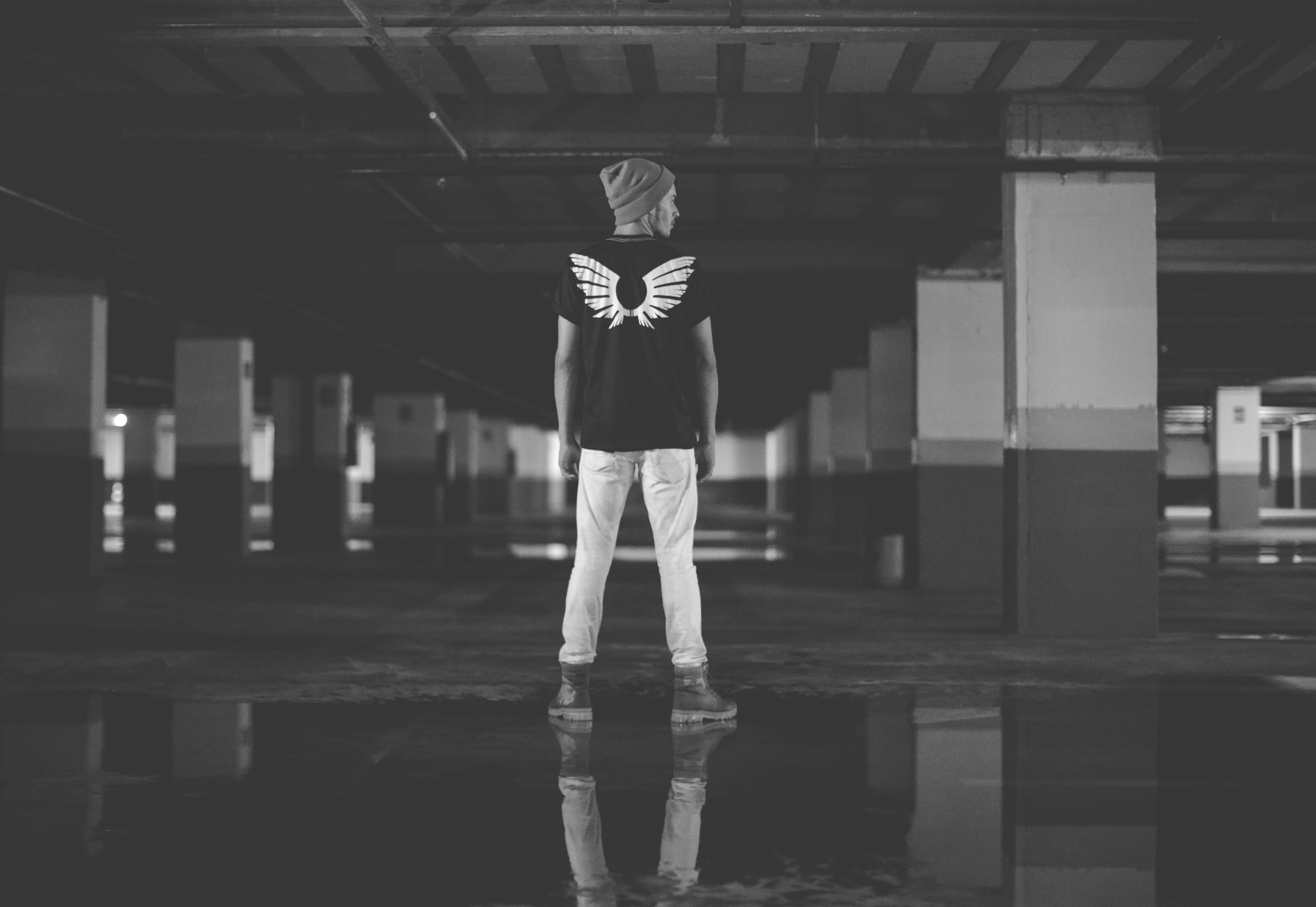 A man with wings on the back of his shirt looking in a parking garage