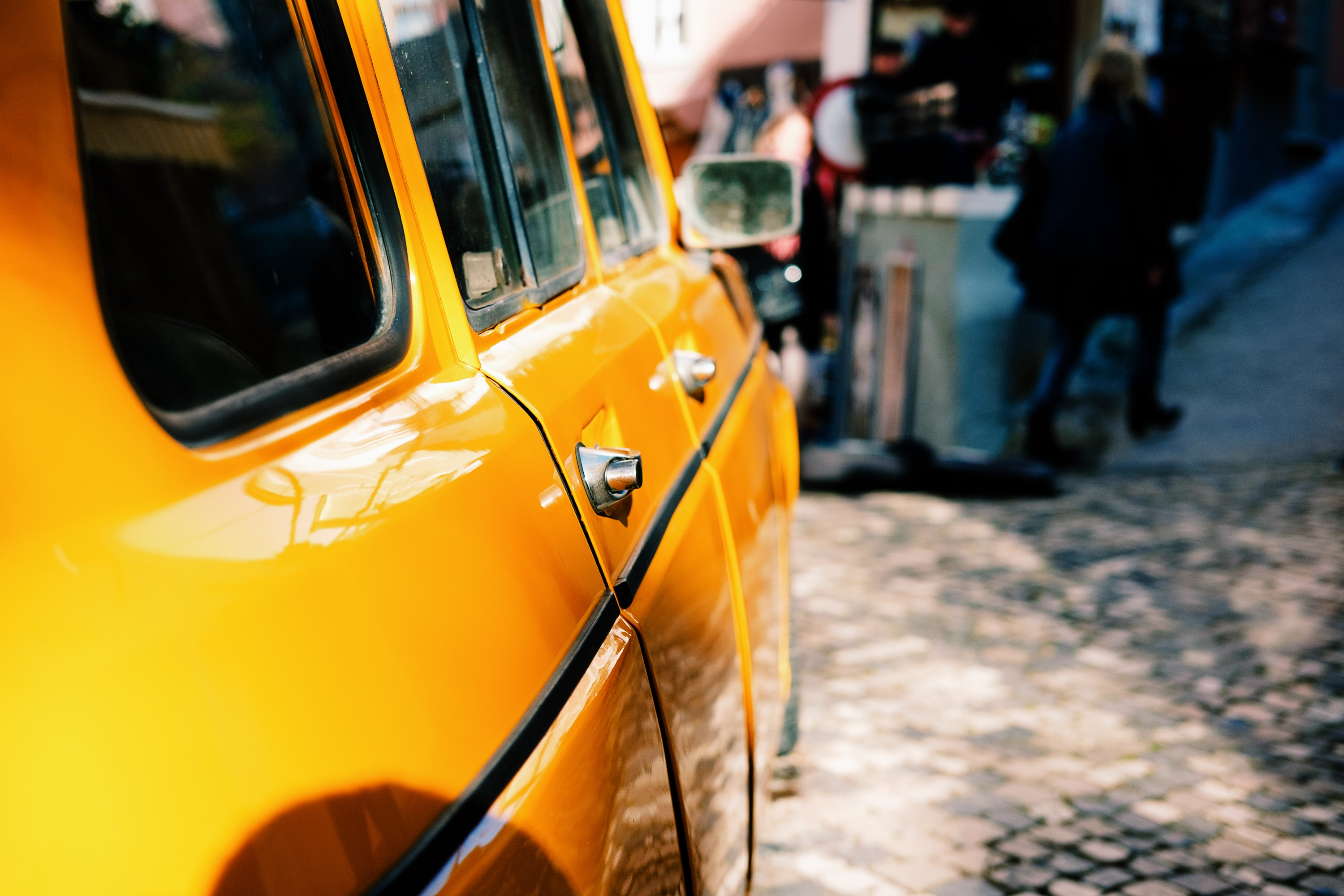 Side of a yellow car with people in the background