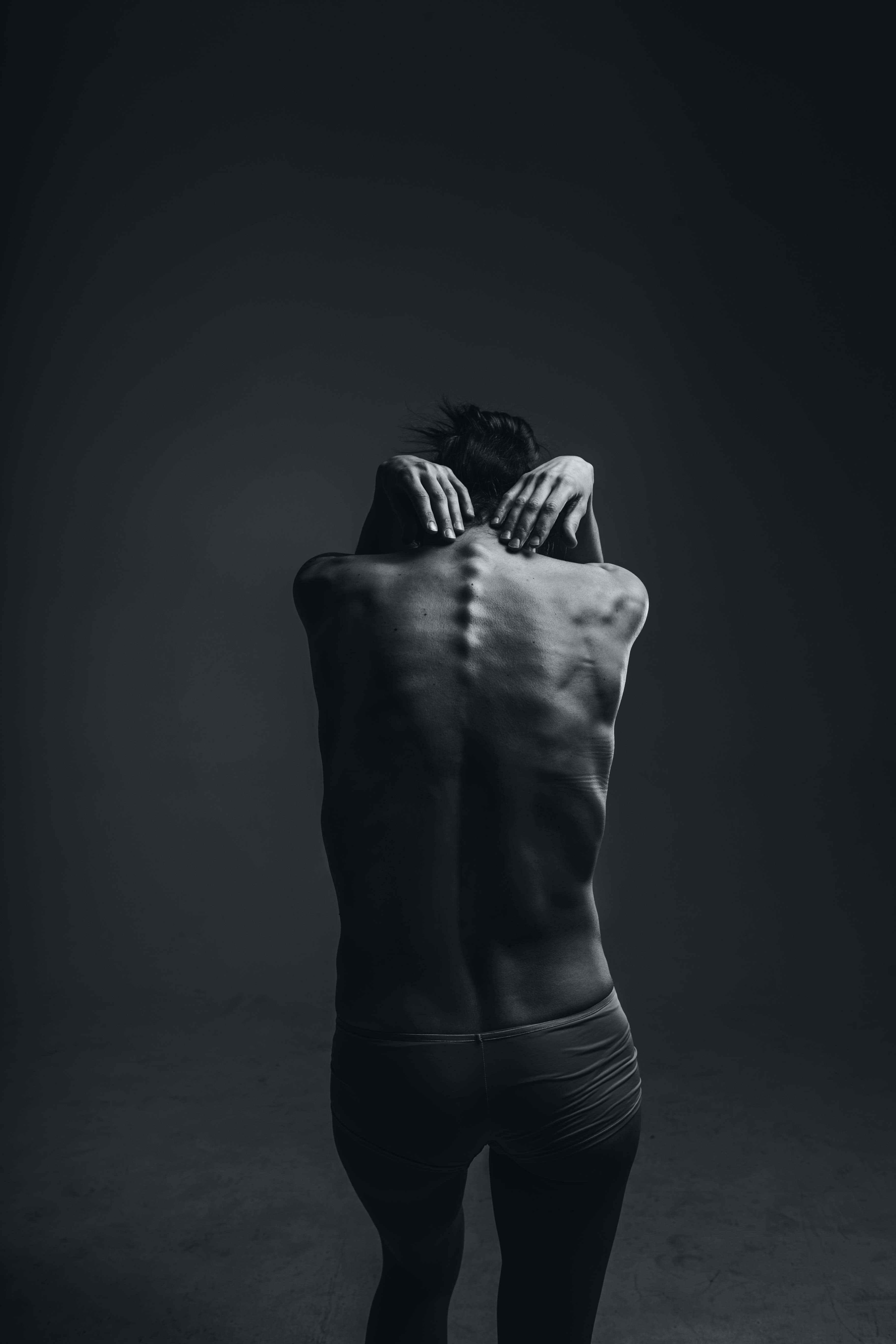 grayscale photograph of person reaching to its back