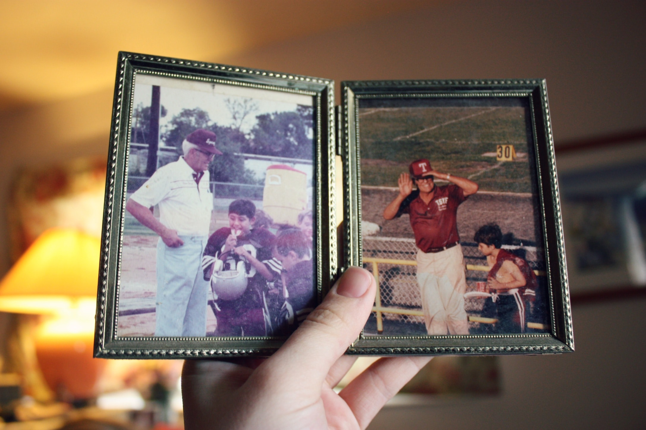 person holding two father and son photographs