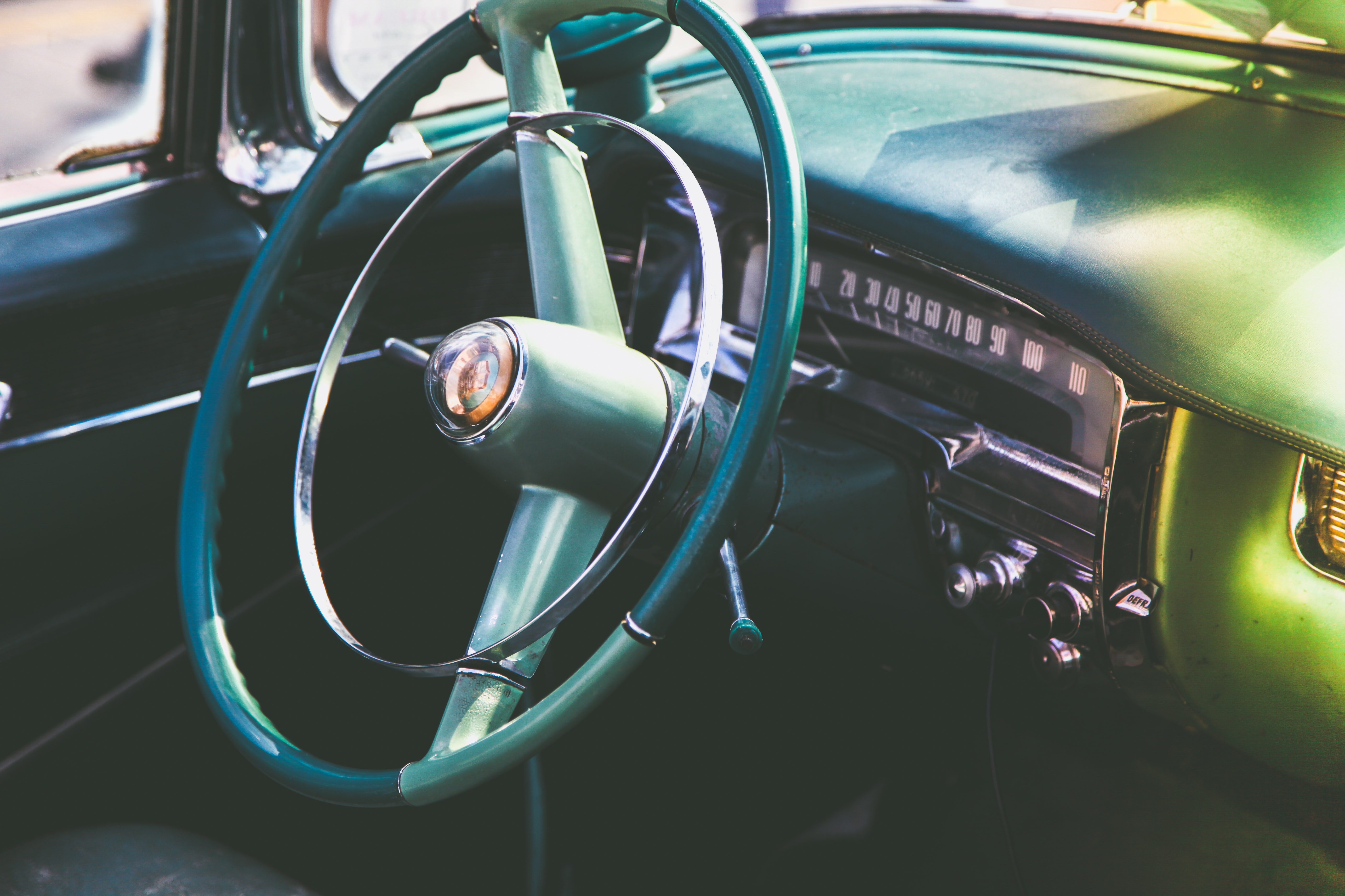A close-up shot of the steering wheel and dashboard of a classic car in London.