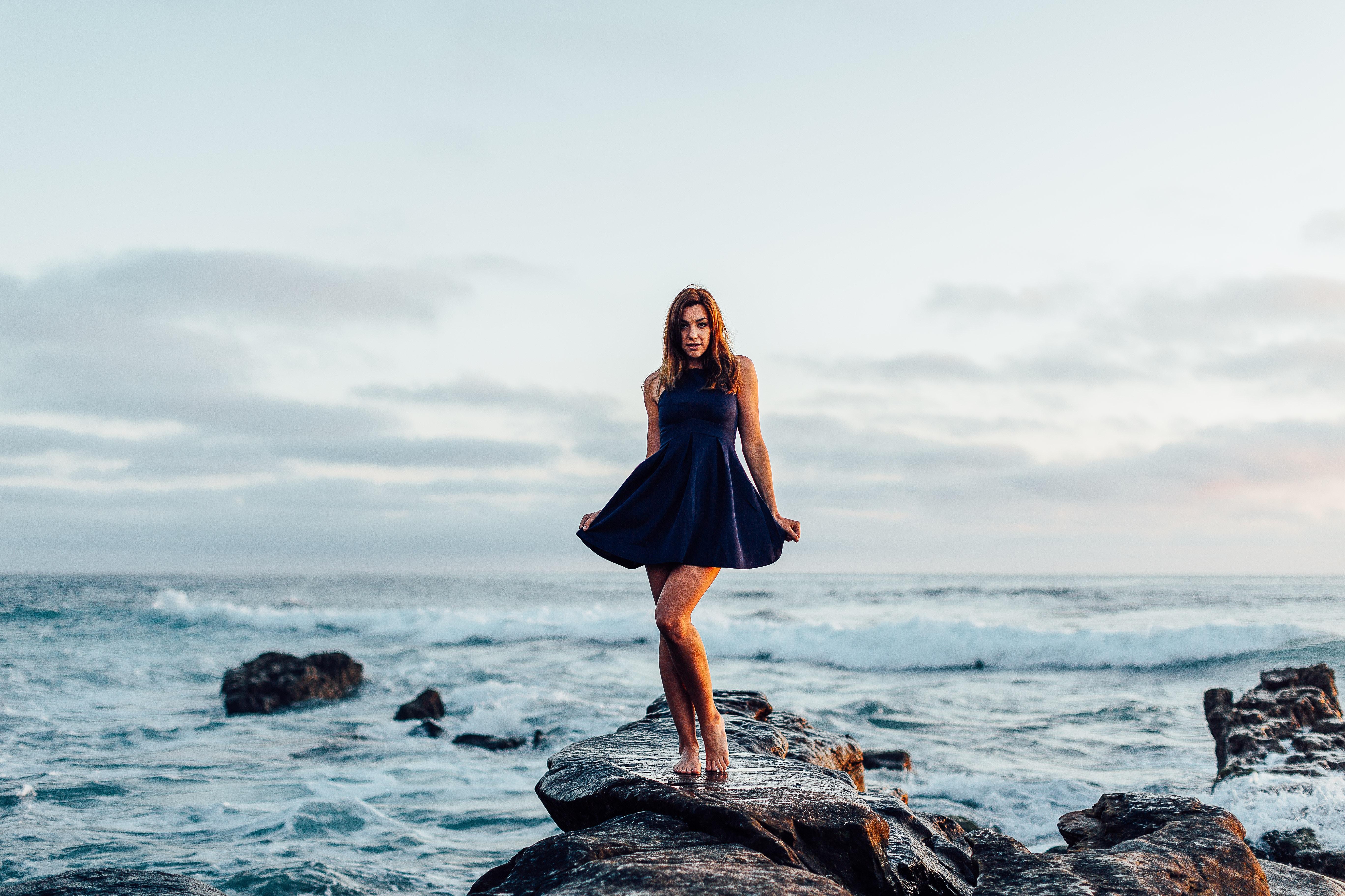 Woman in a dress posing on the shoreline rock at Windansea Beach