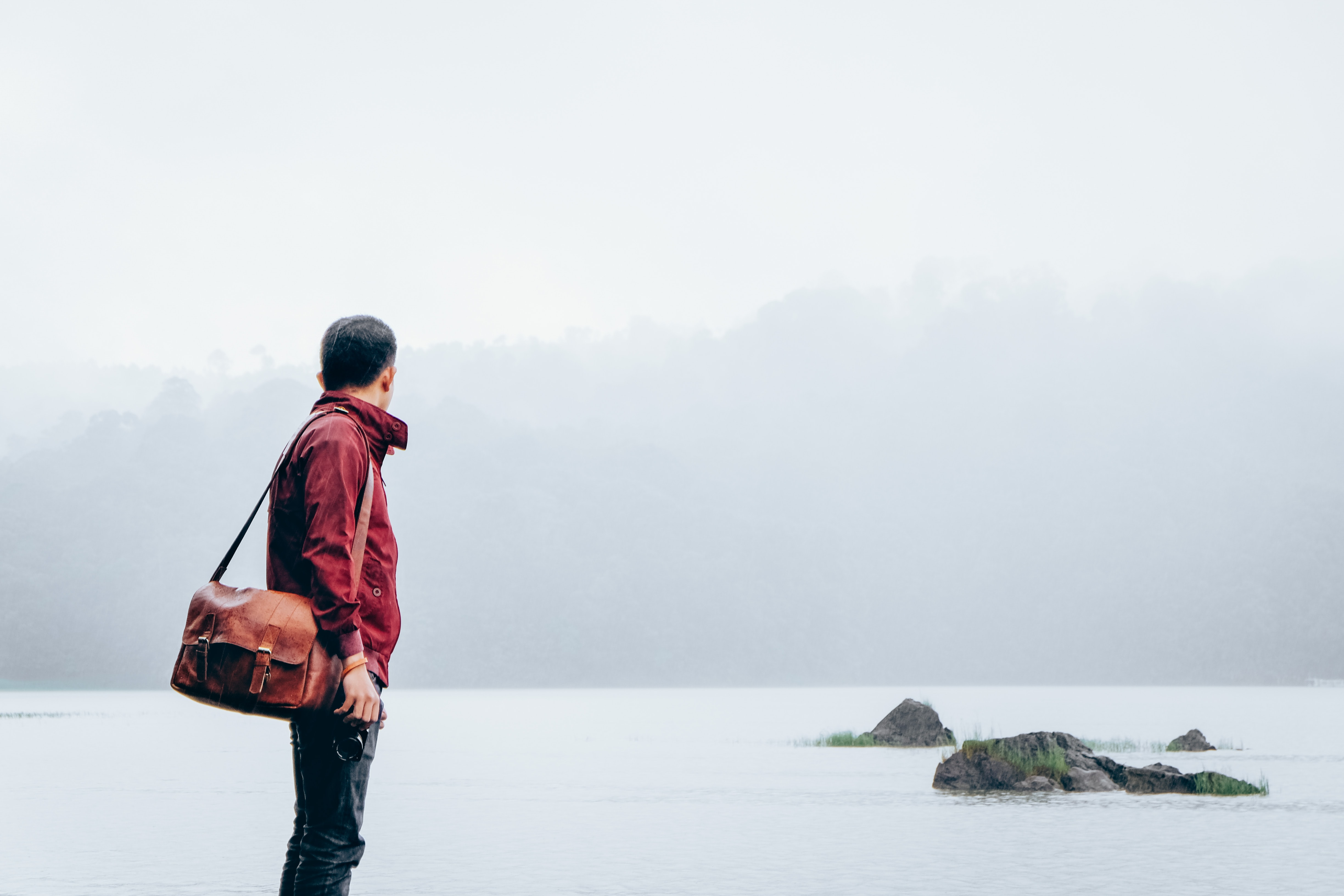 A person wearing a red jacket and brown leather bag looking out at a lake in Ciwidey