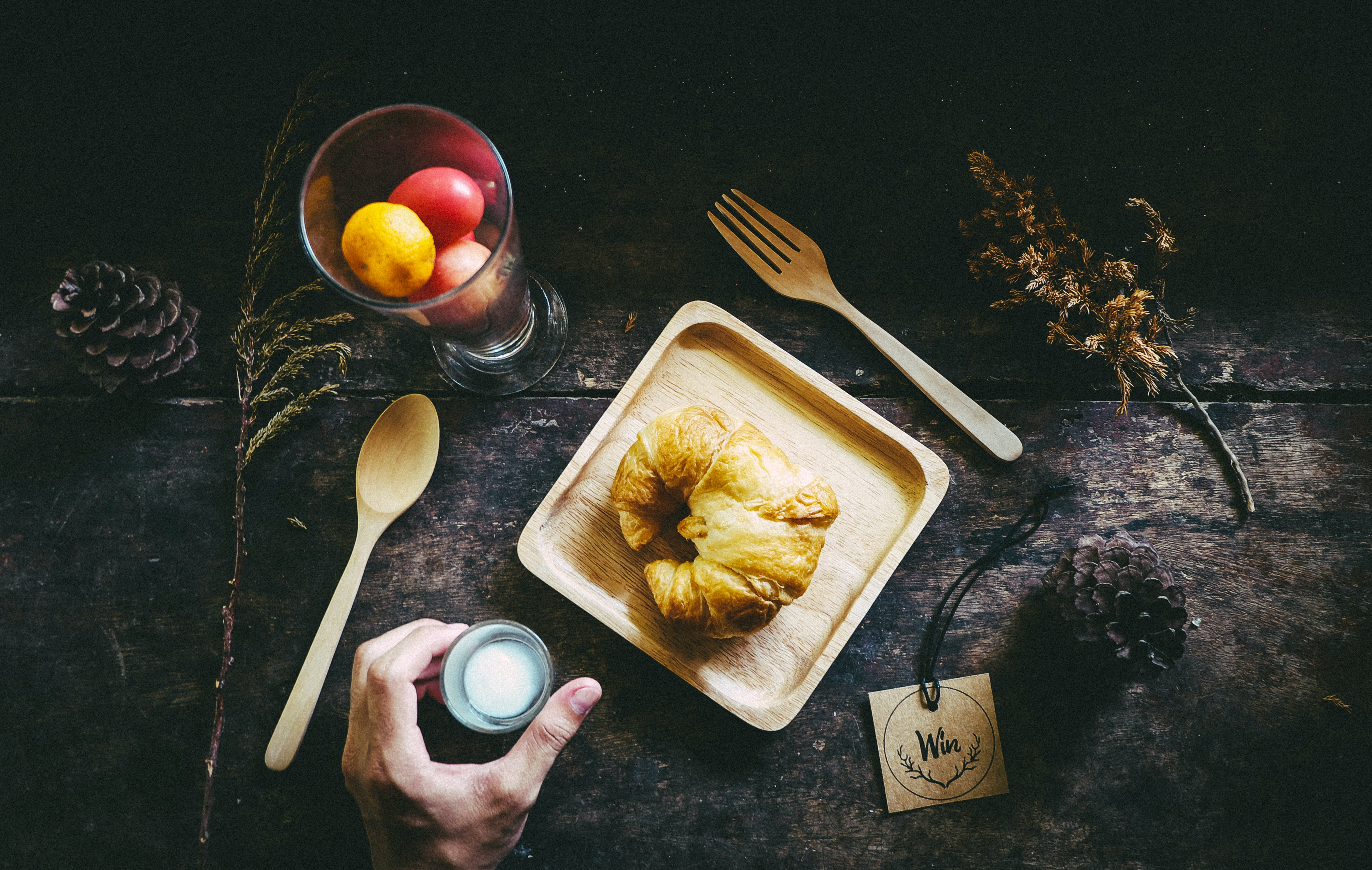 A croissant, fruits, and flatware on a table at Ubon Ratchathani