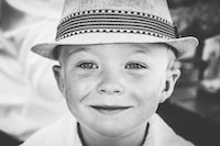 grayscale photography of boy wearing hat