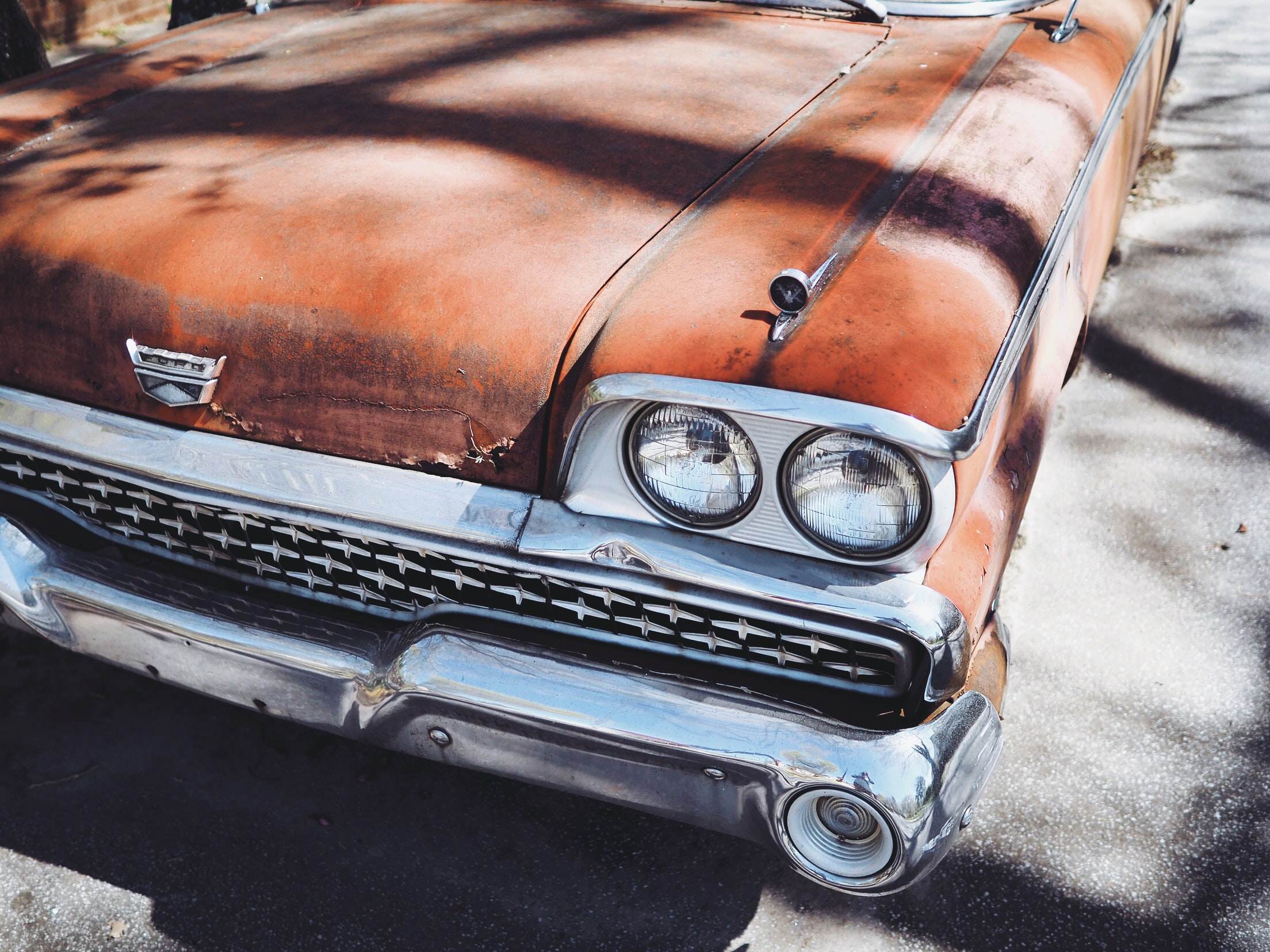 Close up shot of headlight and silver bumper grille on rusty, retro, red Cadillac