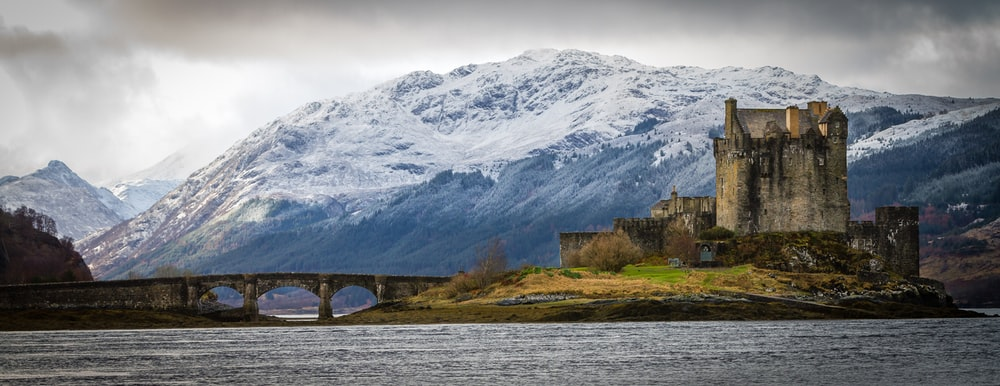A Castle On An Island In Scotland With Bridge And Mountain The Background