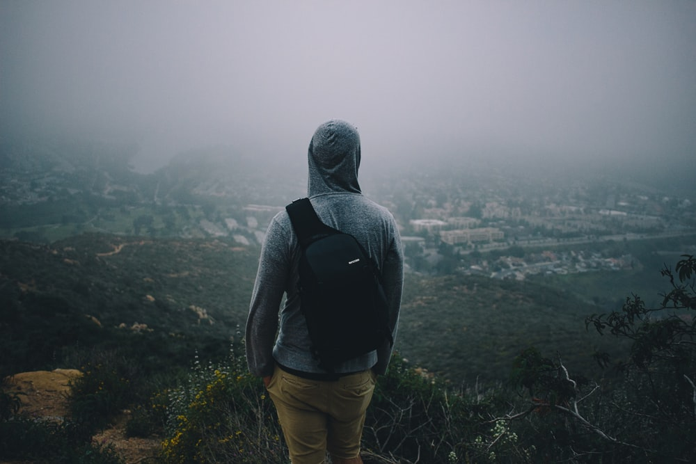 man in gray hoodie with black backpack looking at the city from mountain peek
