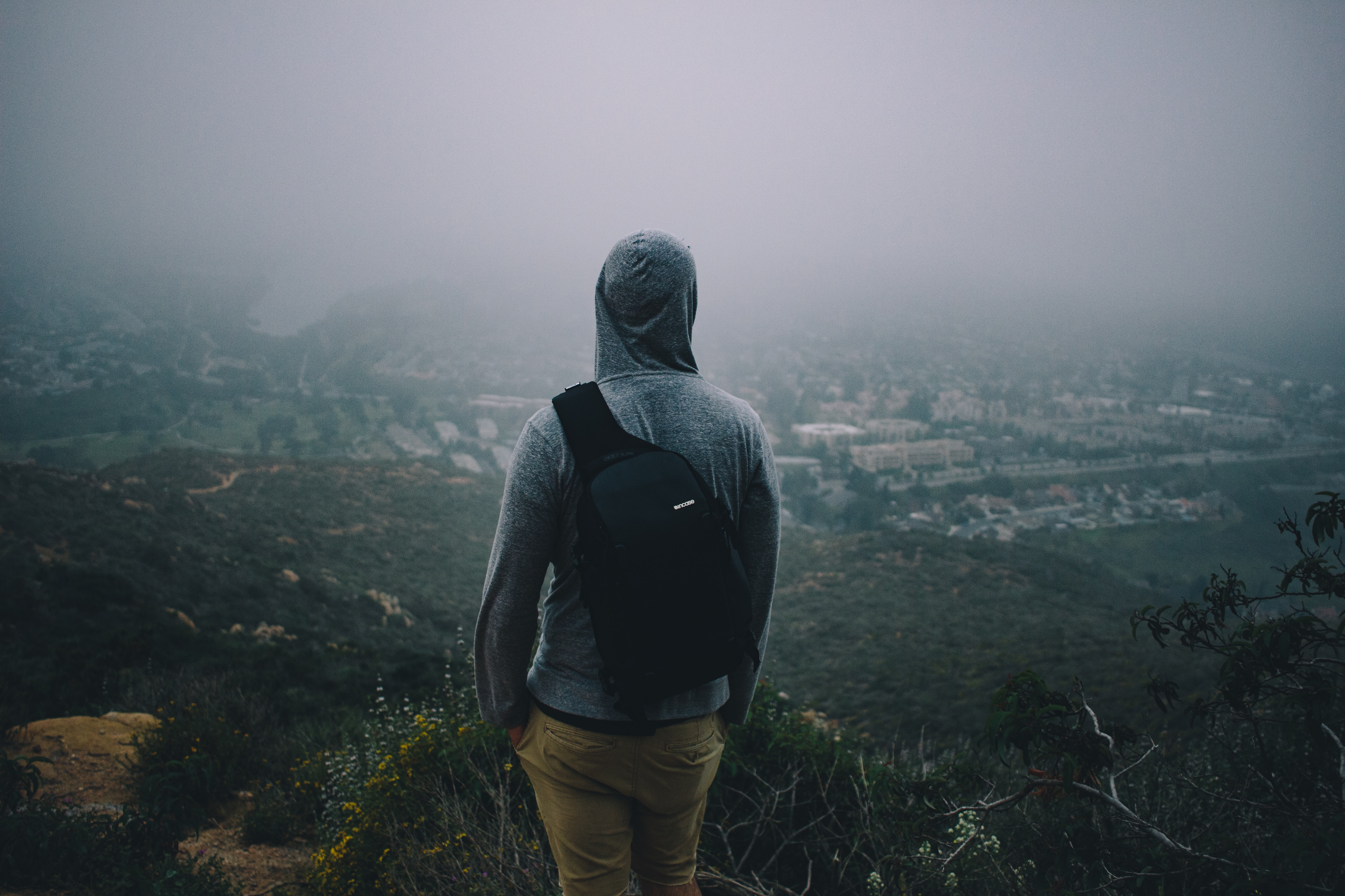 Person looks out at city below after hiking to the top of a rocky bluff