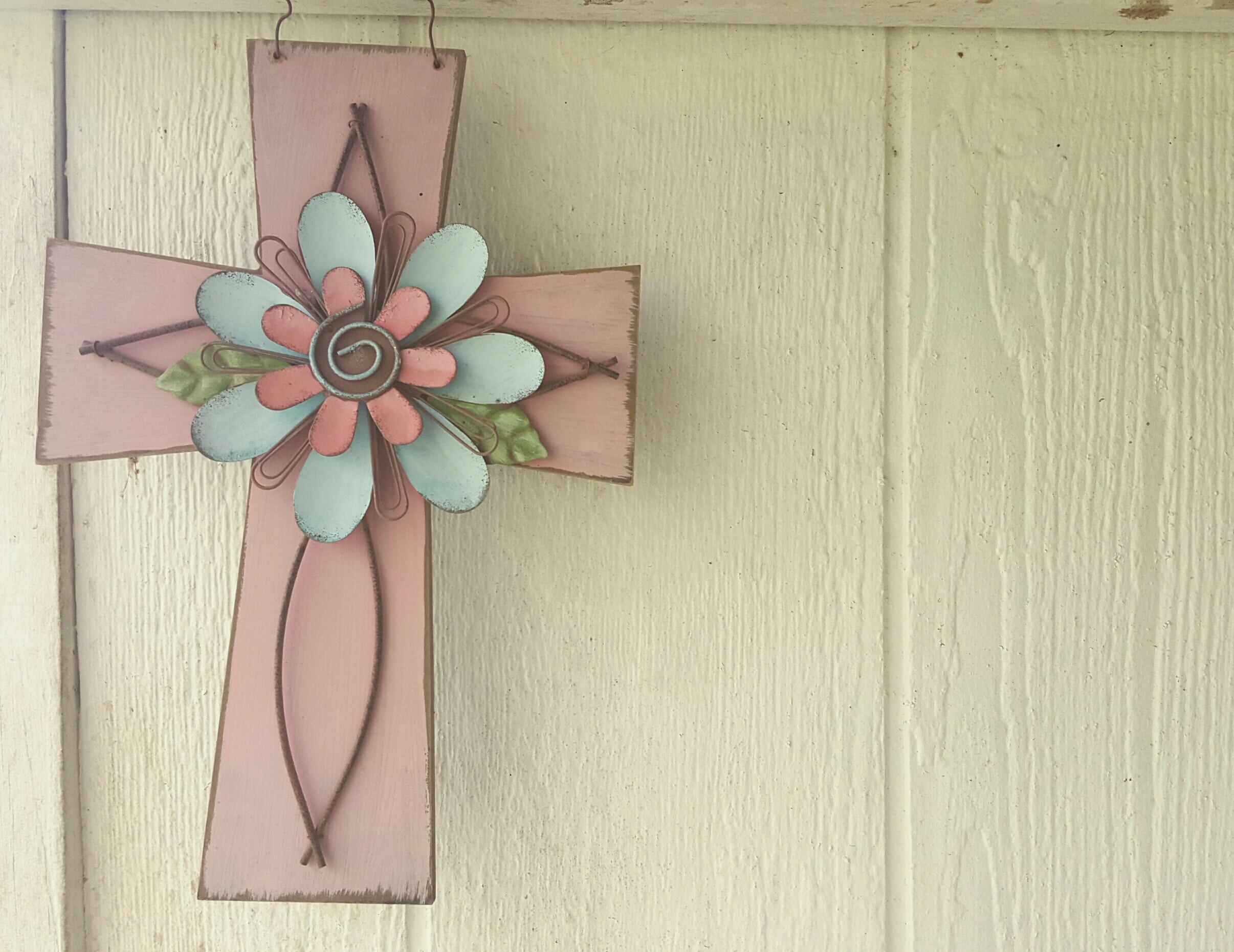 A pink cross with a flower on top.