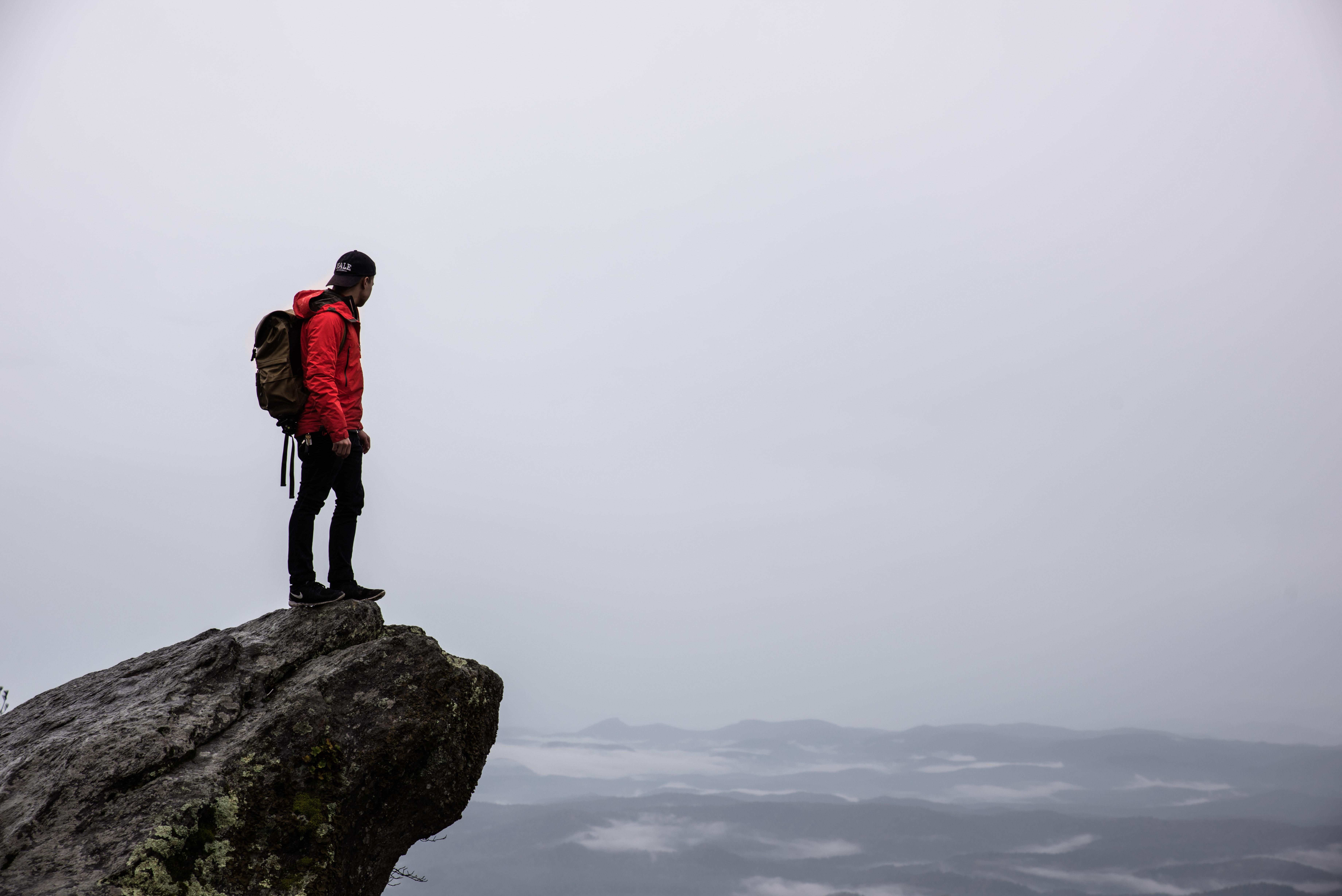 A man with a backpack standing on a ledge overlooking a vast misty plain