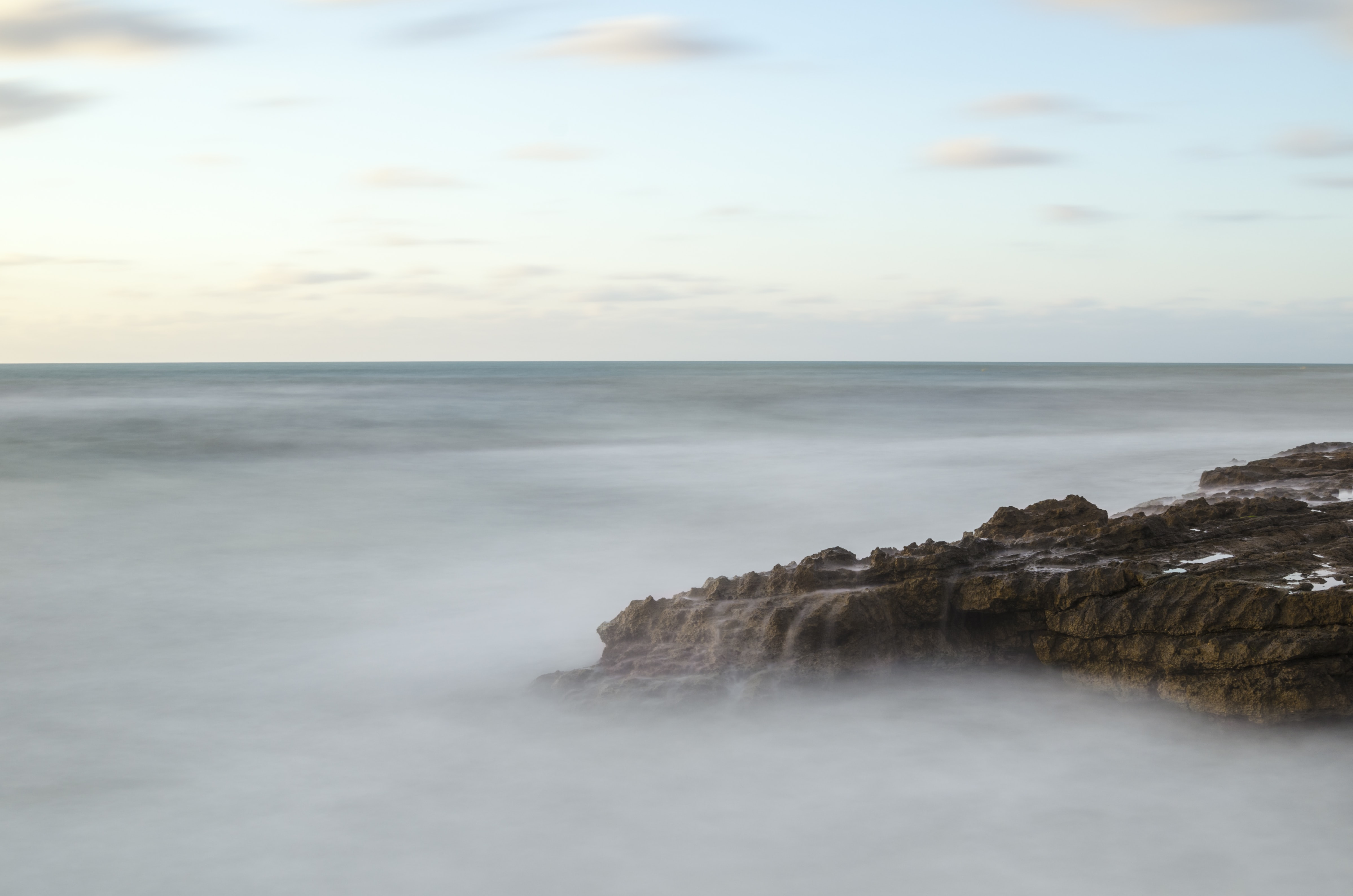 Rocky mountainside on the seashore shrouded in clouds