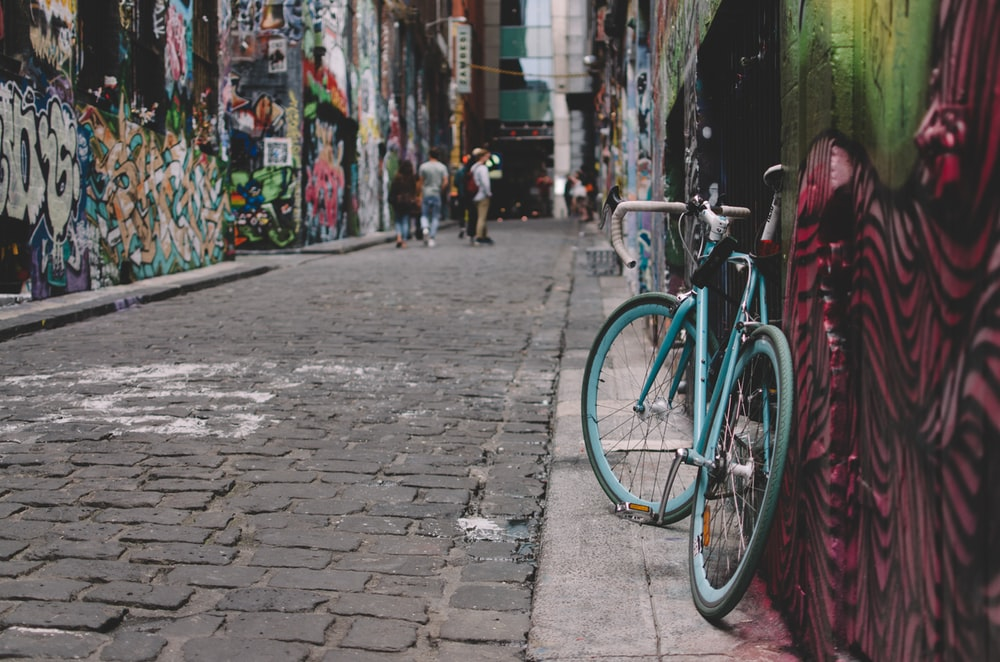 black and blue full-suspension bike parked beside wall