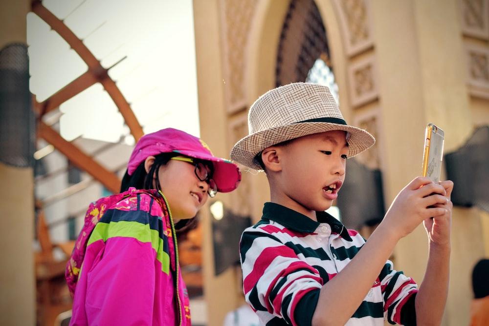 girl watching behind boy holding smartphone