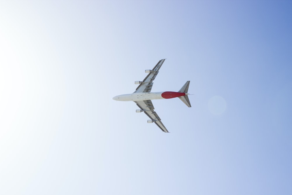 white and red plane in sky during daytime