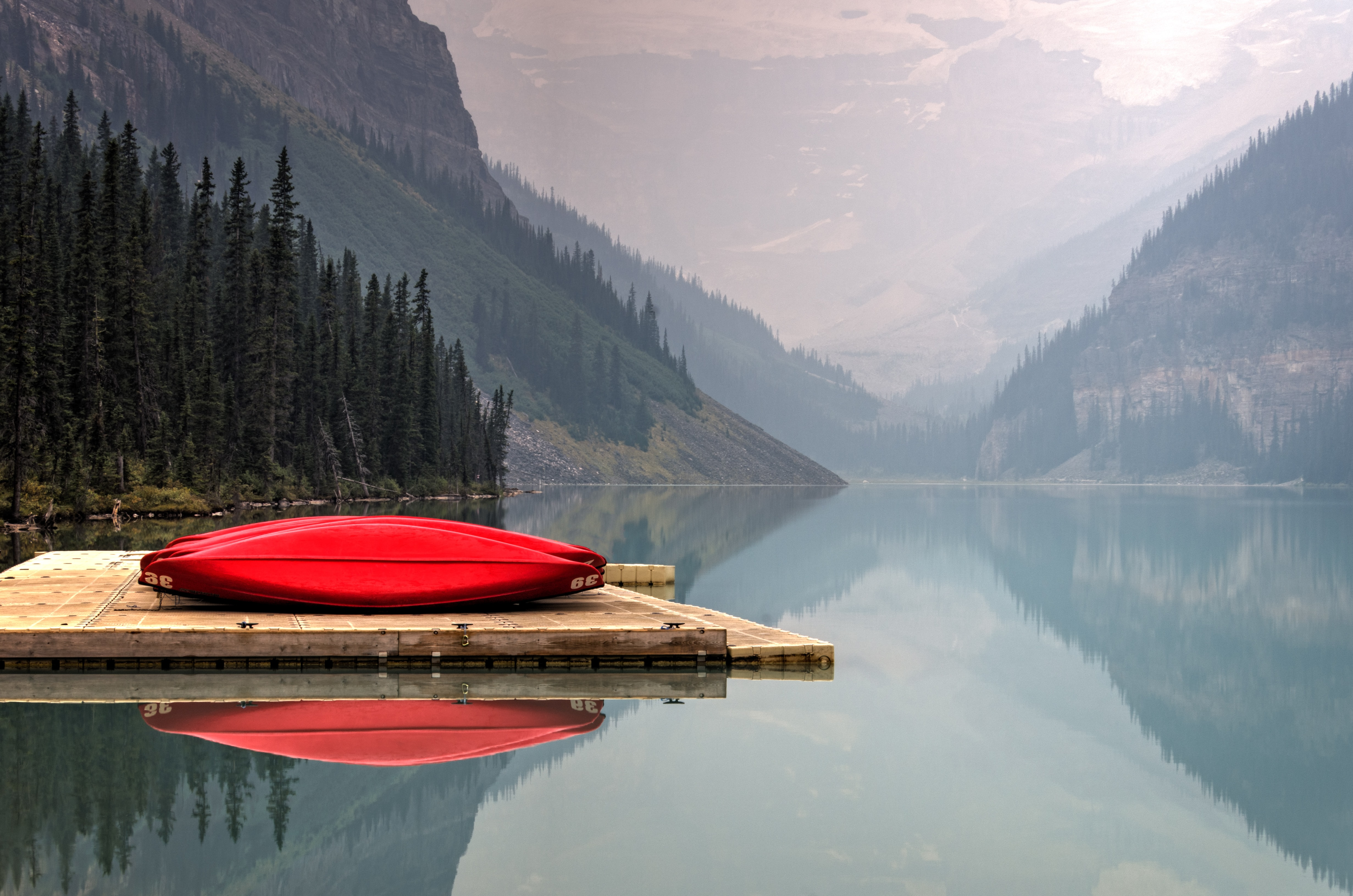 A bright red canoe sits on a wooden dock on a serene Lake Louise