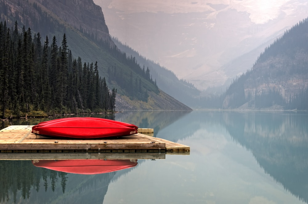 brown floater with red canoe in body of water
