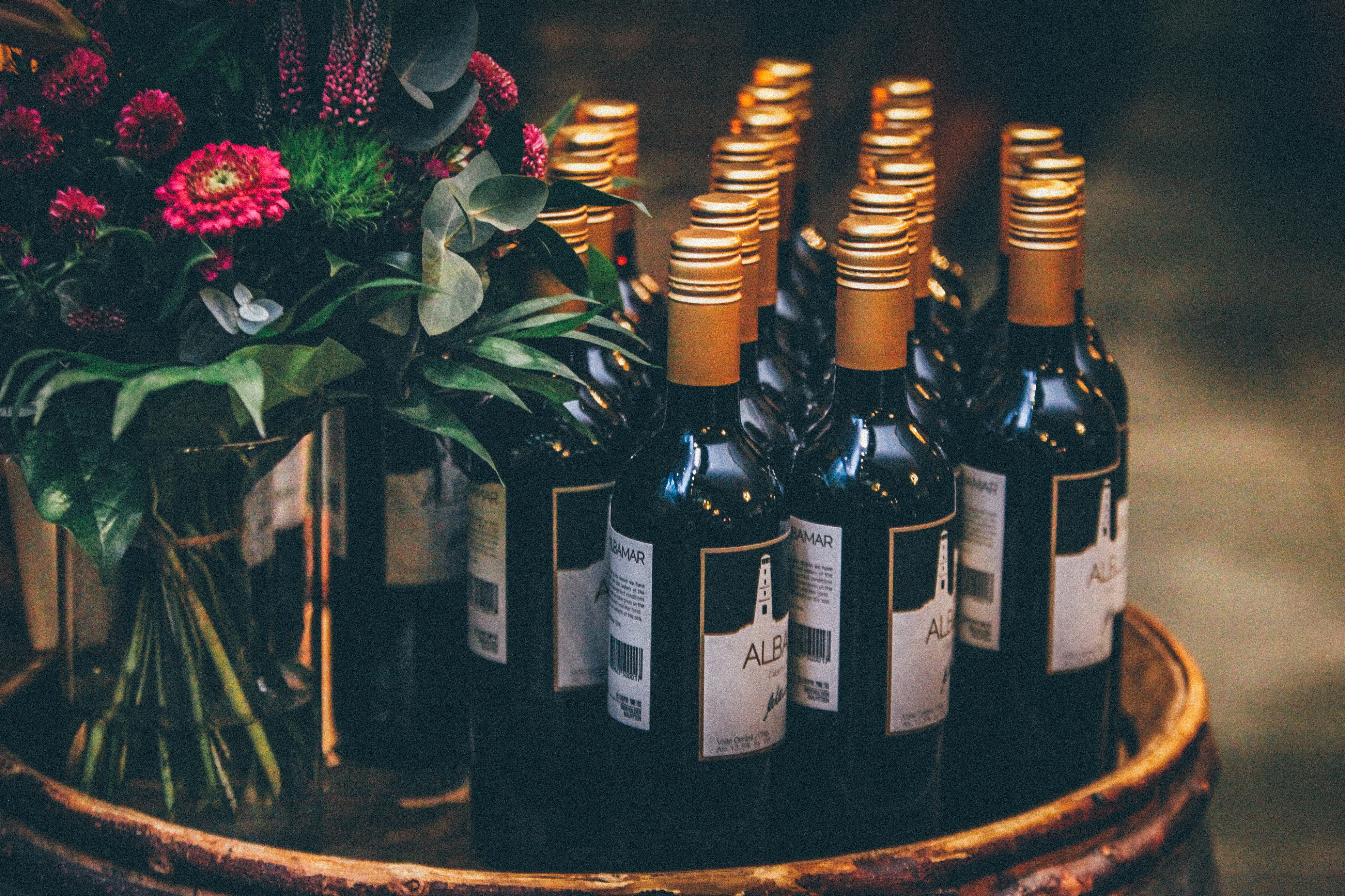 A group of red wine bottles next to a bouquet of roses.
