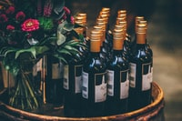 black glass bottles on round table with flowers